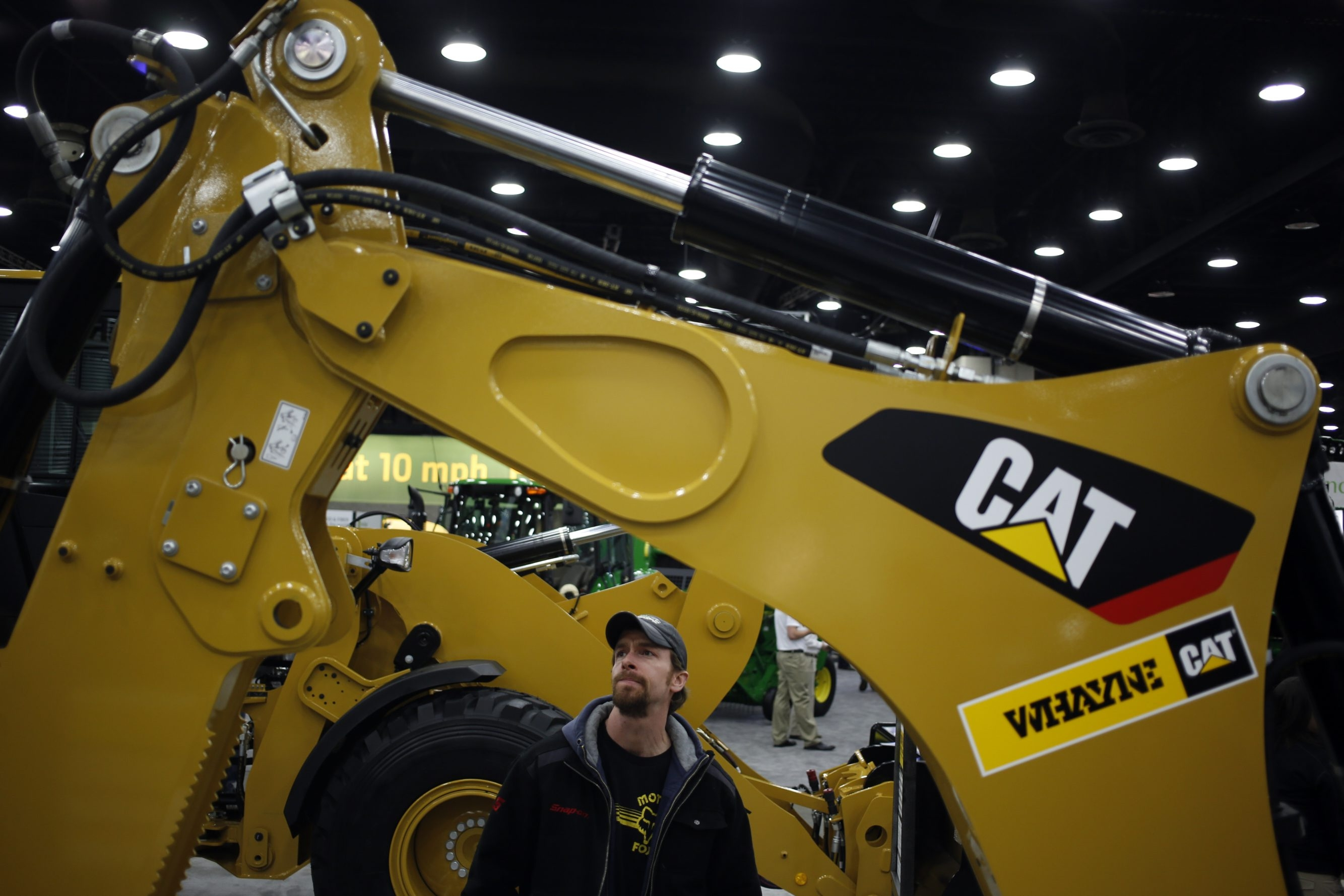 An attendee examines a Caterpillar backhoe loader at the National Farm Machinery Show in Louisville, Ky. The company is facing reduced demand for its equipment as oil prices fall and drillers slash spending.