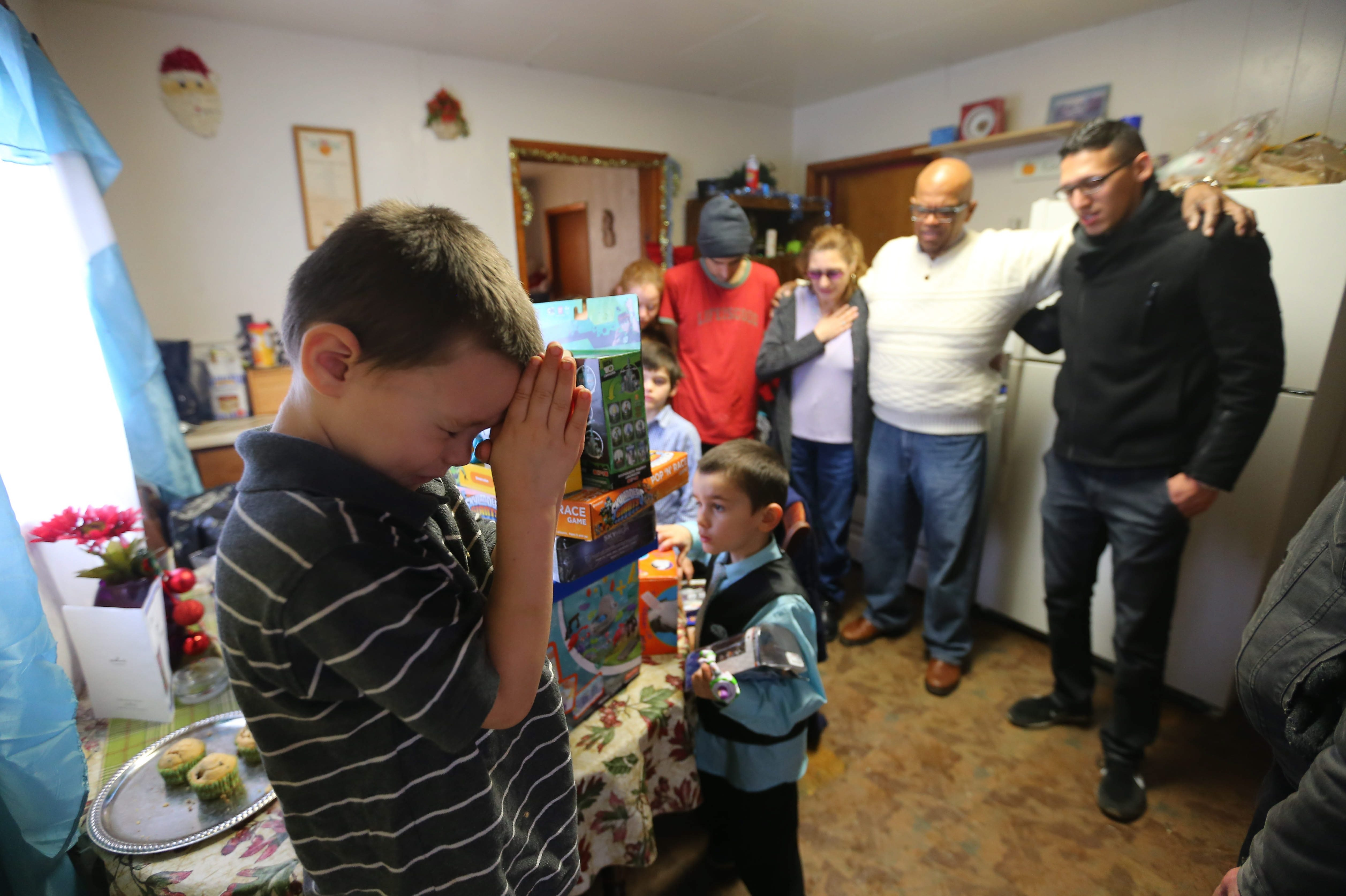 Noah Lopez raises his hands to pray as Pastor Angel Gauthier, in white sweater, leads the Lopez family in a prayer after he brought gifts to their home courtesy of The Buffalo News Neediest Fund and Western New York Holiday Partnership.