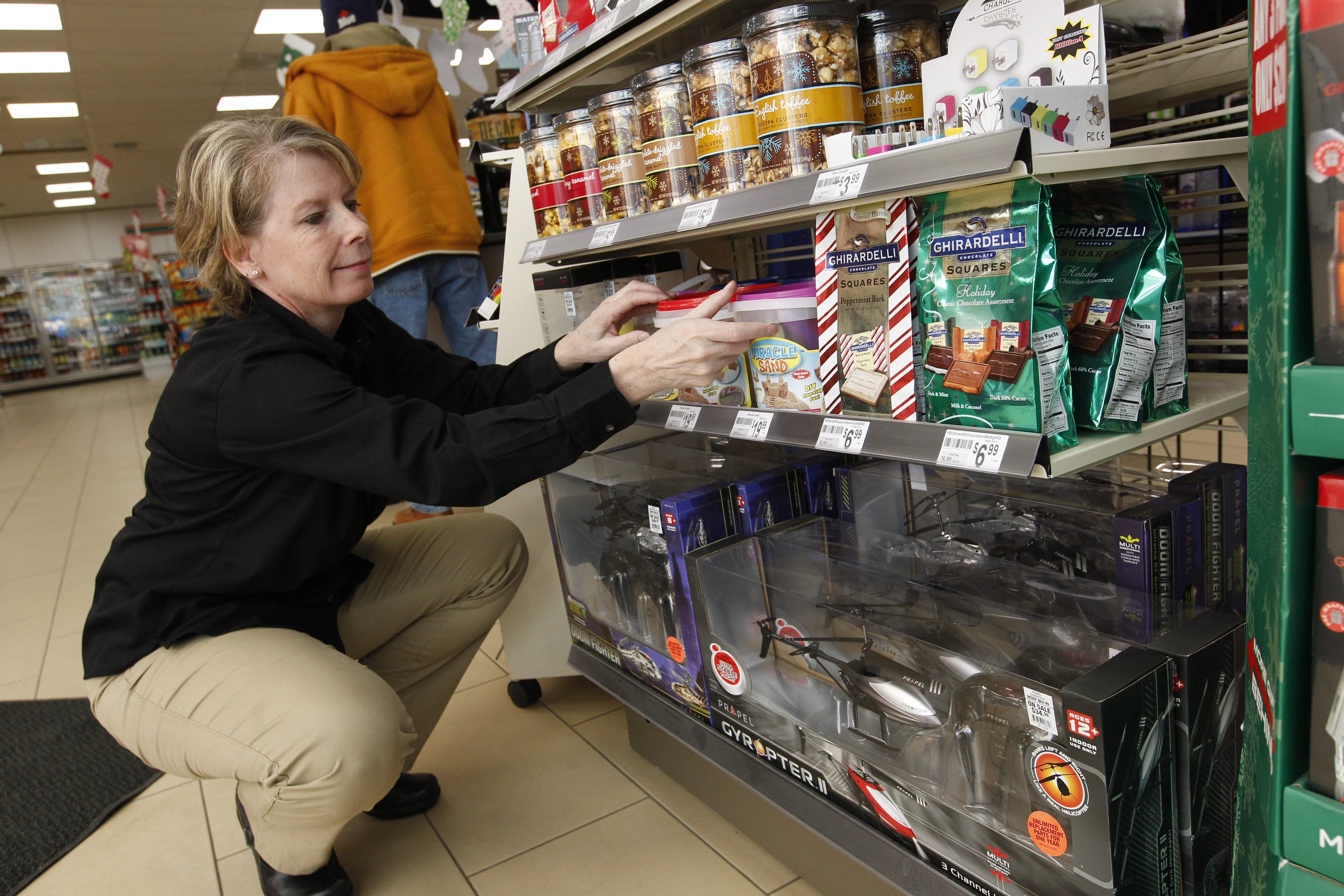 Manager Sherry Wightman arranges a shelf of gift items for the last-minute shopper at the 7-Eleven convenience store in Hamburg.