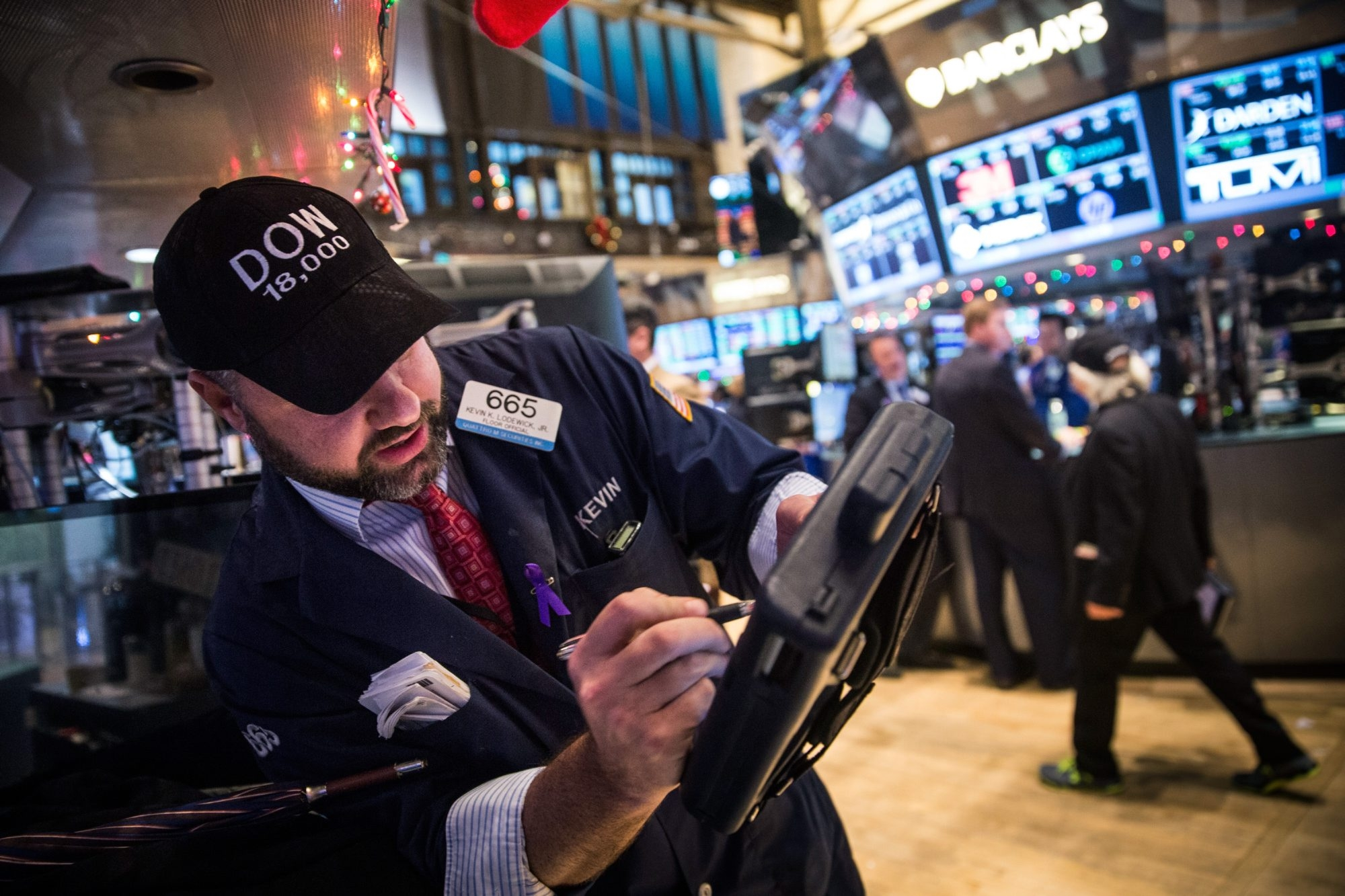 """Traders wear hats that say """"DOW 18,000"""" as they work on the floor of the New York Stock Exchange Tuesday afternoon in New York City. The Dow Jones industrial average crossed a landmark by closing above 18,000 points."""