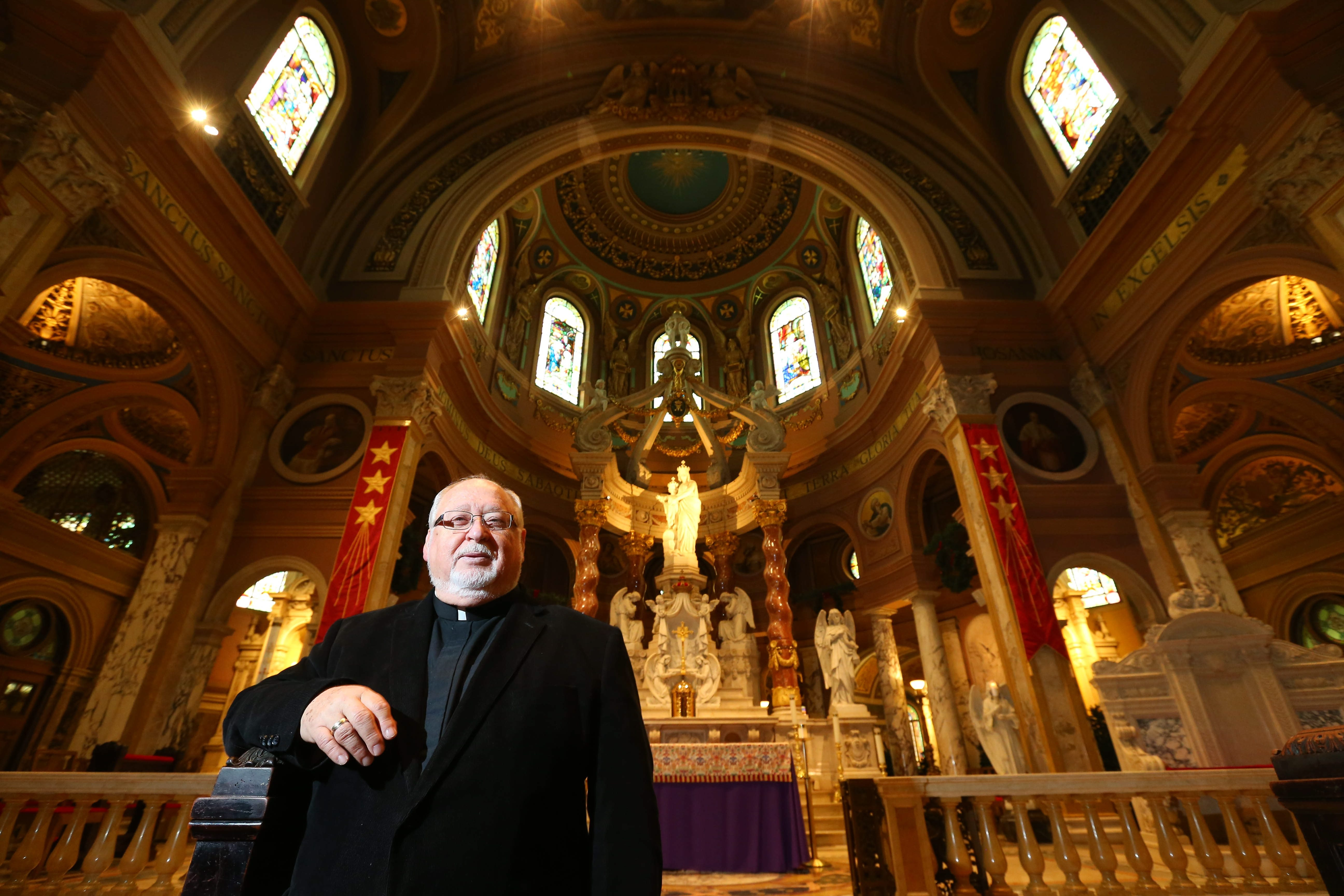 Clockwise from top: Pastor Paul J.E. Burkard shows off the newly renovated Our Lady of Victory Basilica in Lackawanna on Tuesday; One of the 16 stained-glass windows featuring adoring angels that was restored; The scaffolding at the church, which was removed just in time for Christmas celebrations.