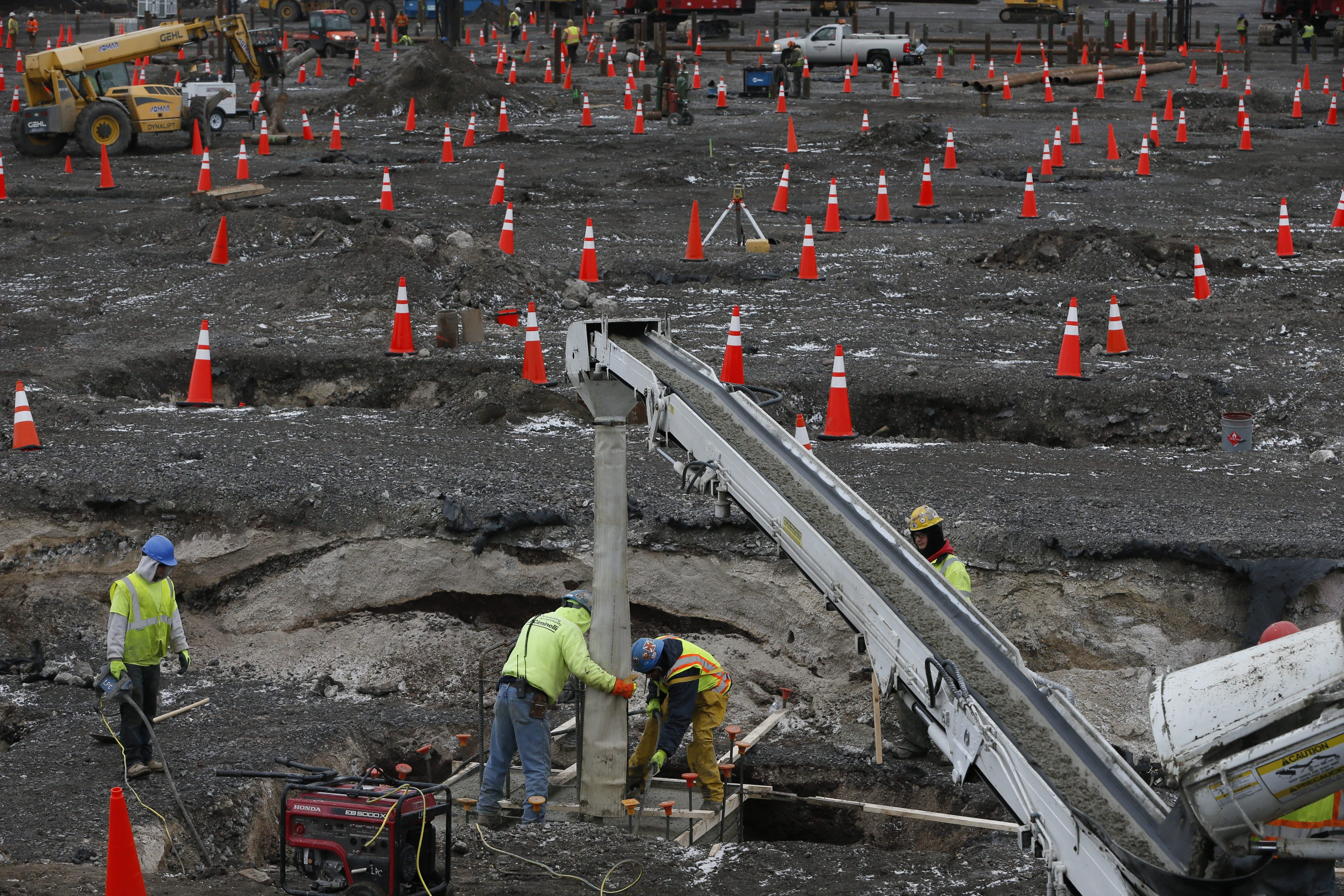Workers pour a concrete cap over a piling at the RiverBend site Thursday as crews drill and insert pilings into the bedrock 70 feet below ground for the foundation of the SolarCity manufacturing facility that will be built there. Photos by Derek Gee/Buffalo News