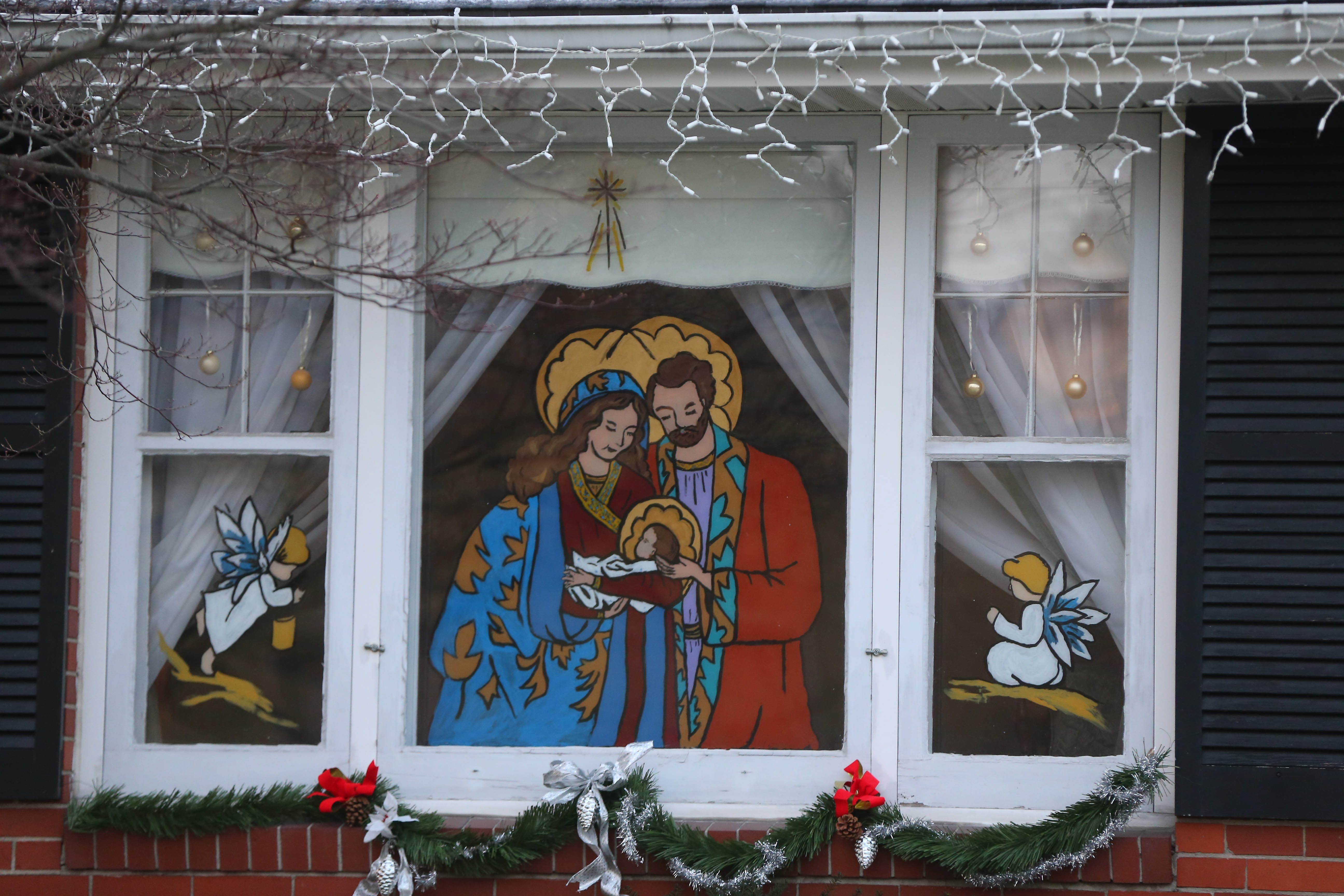 Carolyn Nosky painted this picture of the Holy Family on her front window to celebrate the holiday as she has every year since 1954.