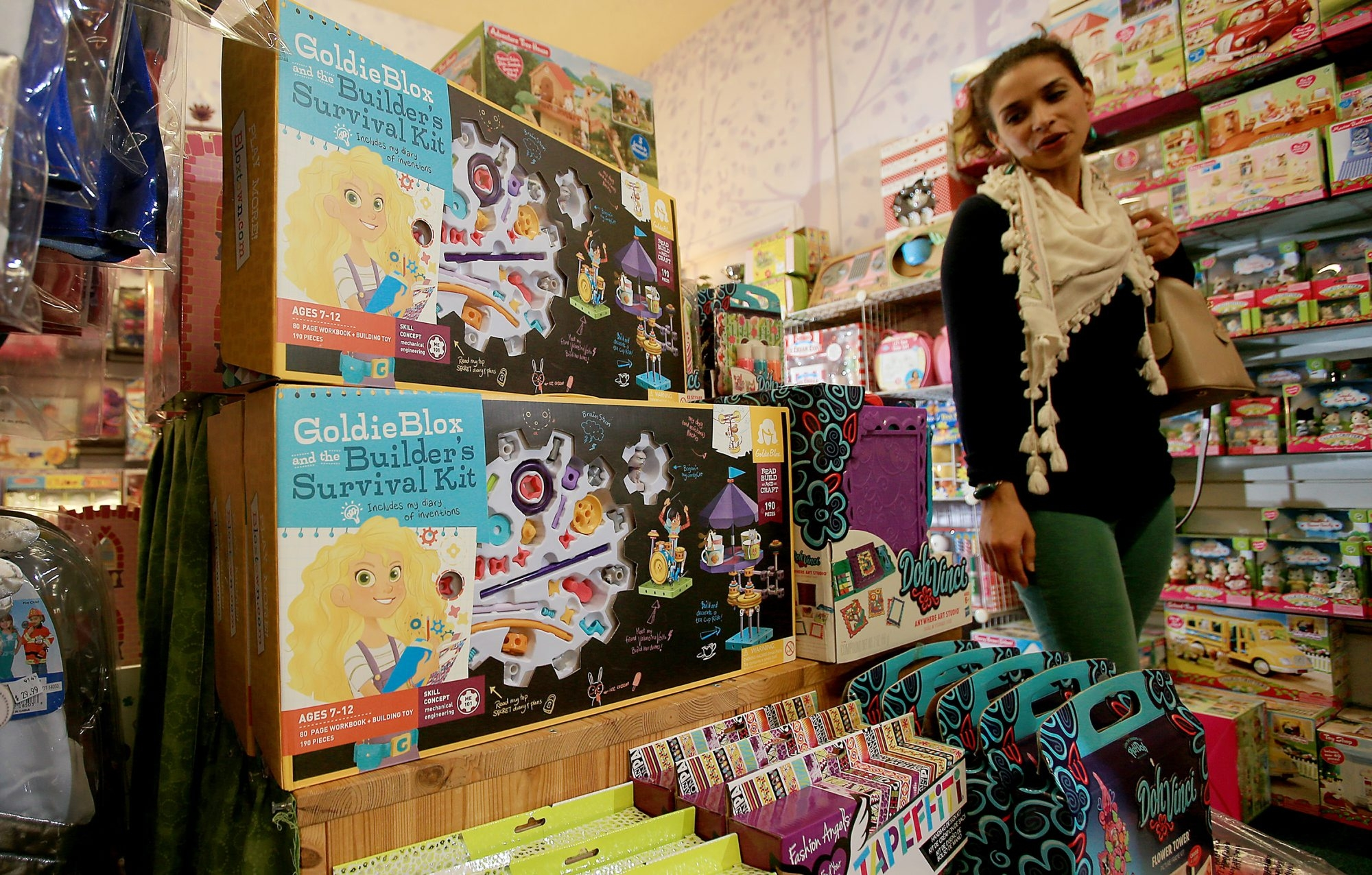 Dulce Aguilar shops for a gift at the Dinosaur Farm, an independent toy store in South Pasadena, Calif., that has seen brisk sales in construction toys for girls such as GoldieBlox, pictured.