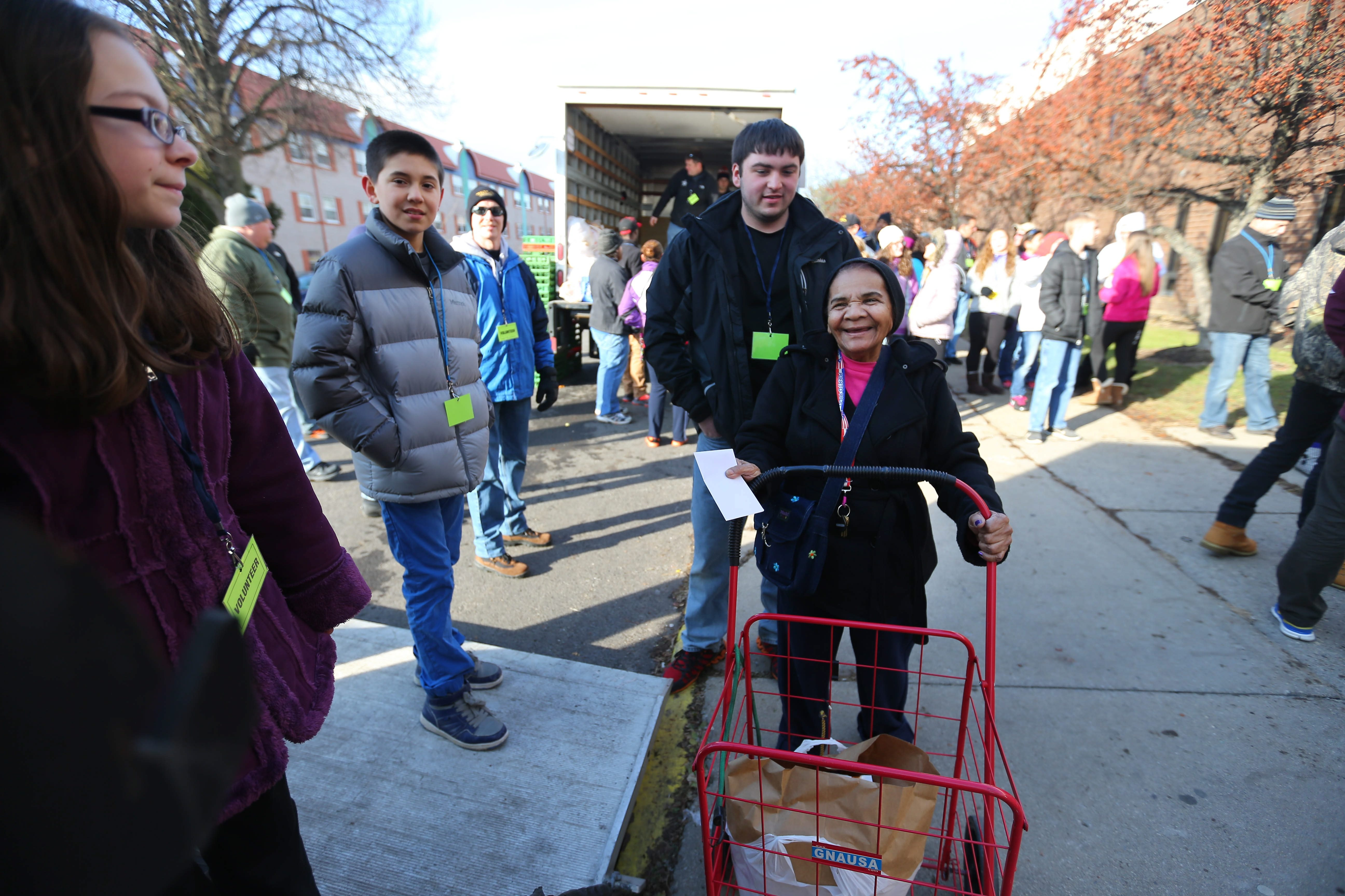 """From left, Makayla Lehner, John Woodin and Evan Miranda enjoy the smiling face of a woman after they put a bag of food in her cart during Saturday's """"Boxes of Love"""" toy and food distribution on Buffalo's West Side."""