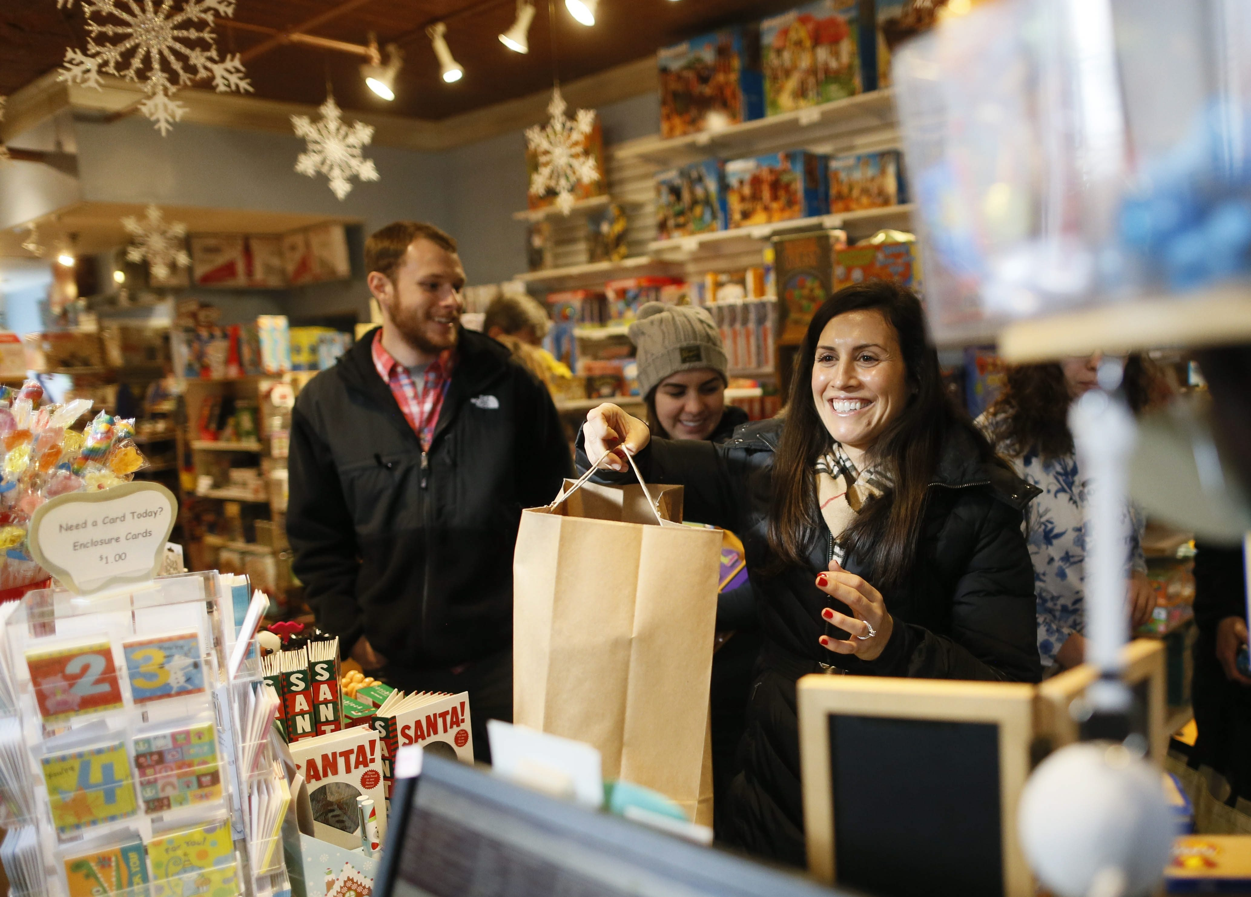 """Angela Mancini of Clarence picks up some presents at TreeHouse toy store on Elmwood Avenue on the day before """"Panic Saturday."""""""