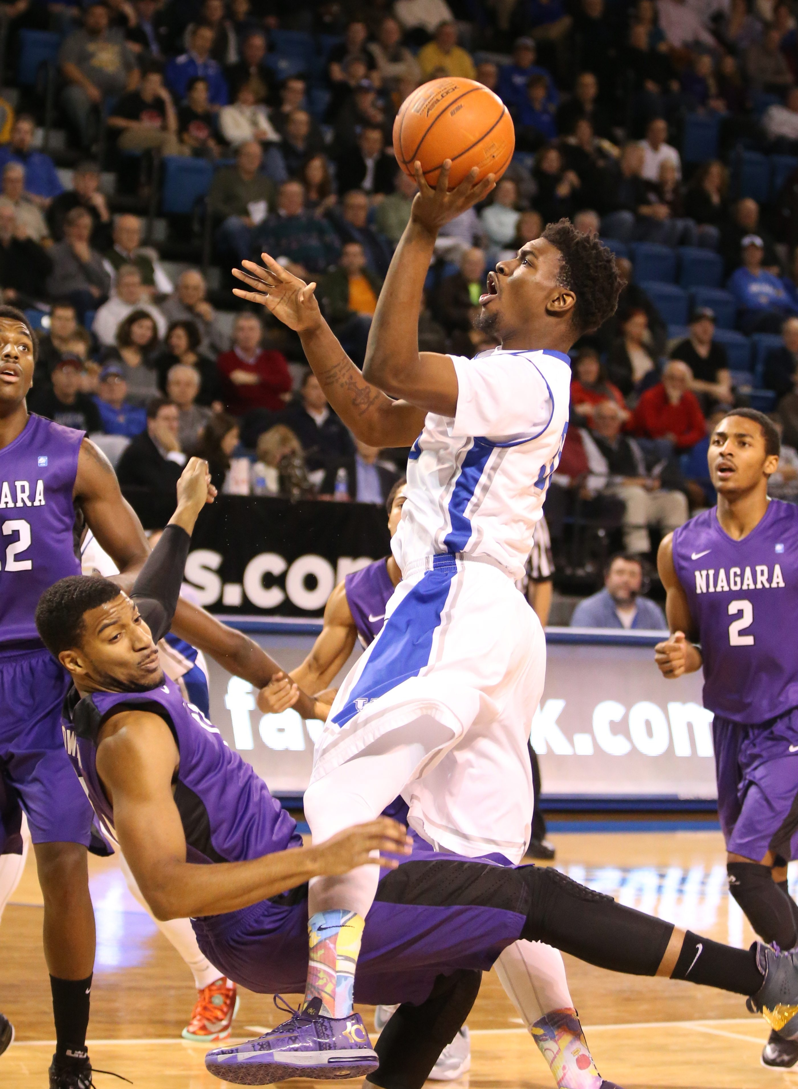 UB forward Xavier Ford puts up a left-handed shot to score two points over a falling Ramone Snowden of Niagara. Ford came off the bench to score 11 points and get 13 rebounds.