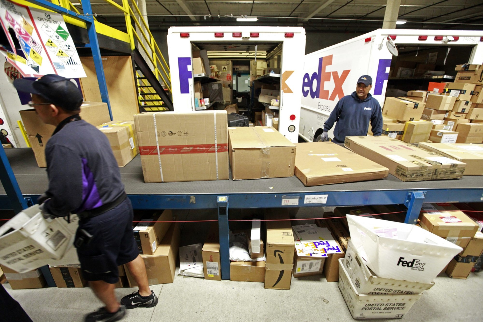 Workers at the FedEx facility in San Francisco watch for their designated packages, moving down a conveyor belt, to be loaded for delivery on Monday, the busiest shipping day of the year. Delivery services are hoping this season goes smoothly.