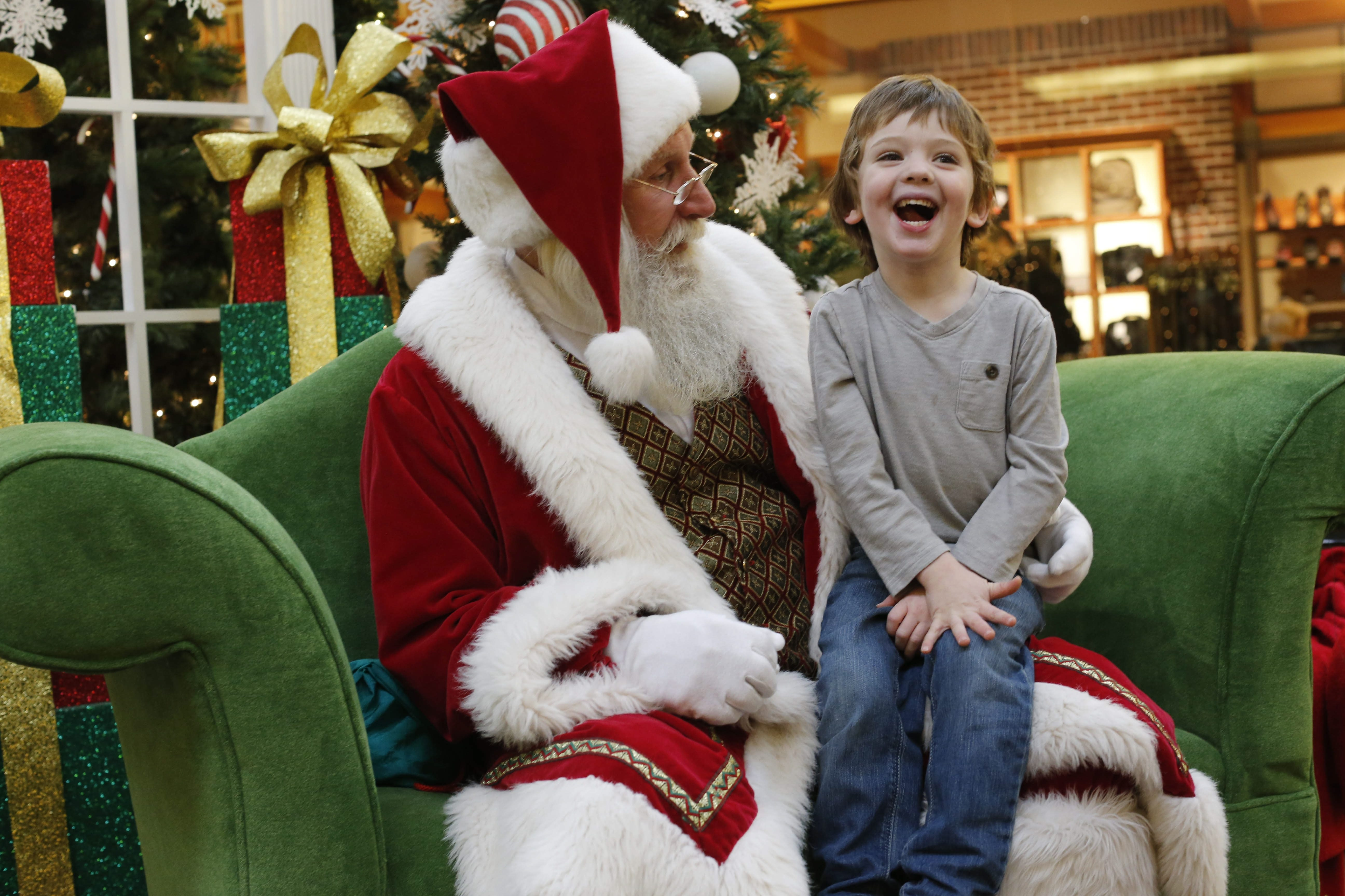 Nervous and excited, Keaton Braun, 4, of Lakeview passes on his Christmas wishes to Santa Claus at the Walden Galleria mall, Wednesday, Dec. 17, 2014.  Mike Stroh is a natural in the role of Santa, which he wears on and off the clock--year round.