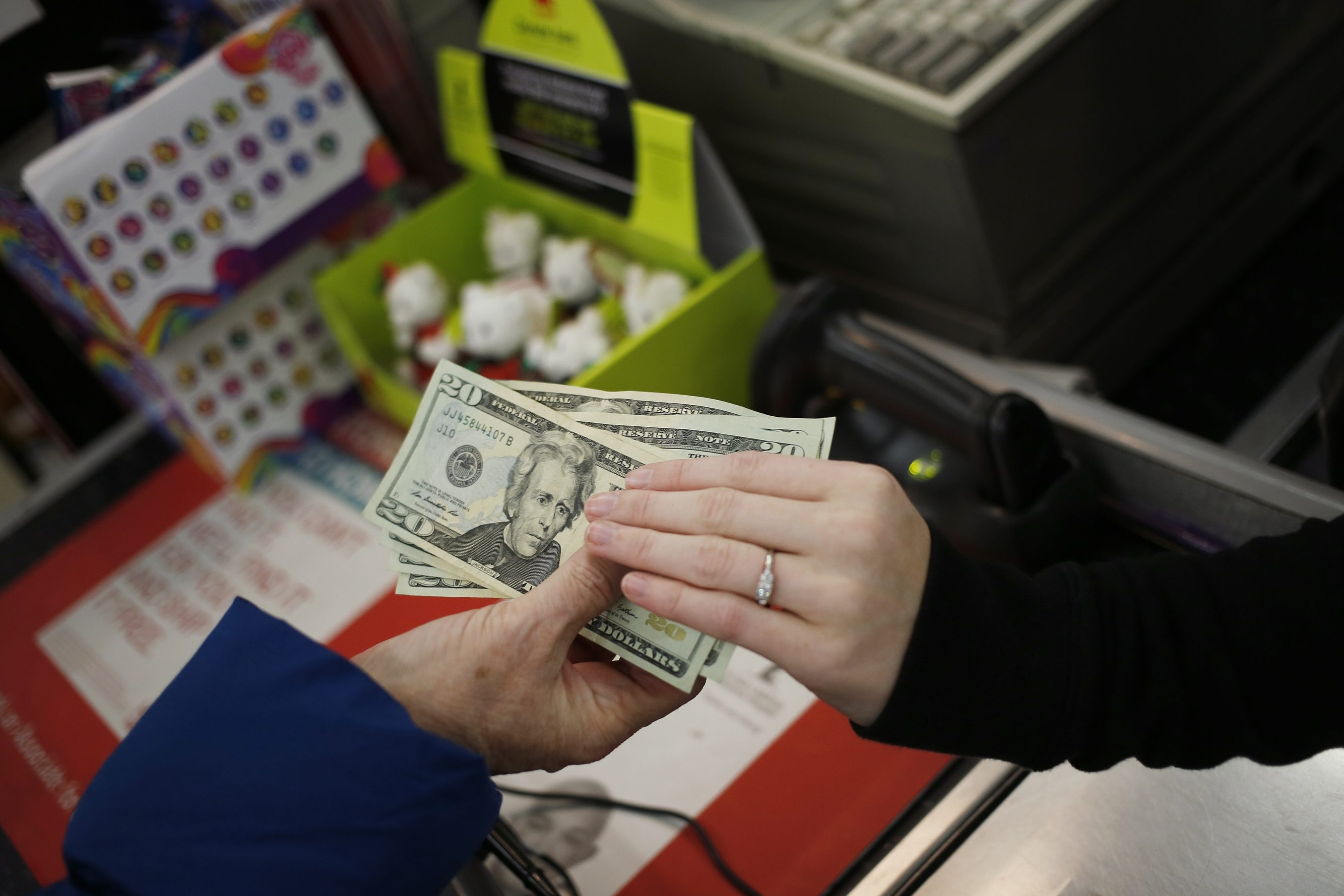A customer, left, hands over U.S. twenty dollar bills as she pays for her purchases at the checkout inside a Kmart discount store, operated Sears Holdings Corp., ahead of Black Friday in Frankfort, Kentucky, U.S., on Thursday, Nov. 27, 2014. An estimated 140 million U.S. shoppers are expected to hit stores and the Web this weekend in search of discounts, kicking off what retailers predict will be the best holiday season in three years. Photographer: Luke Sharrett/Bloomberg