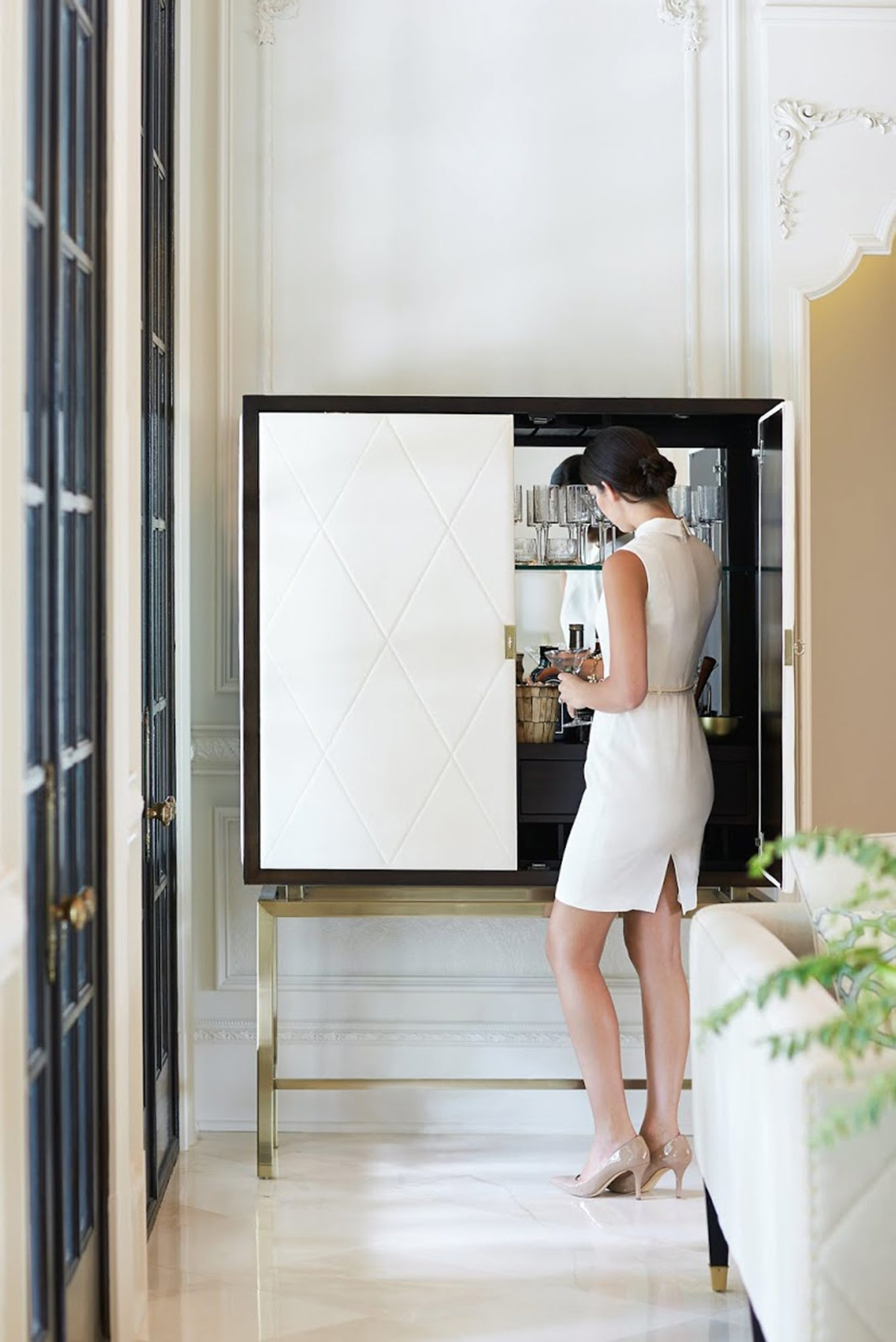 White leather doors accent the elegant bar cabinet from Bernhardt's Jet Set collection.