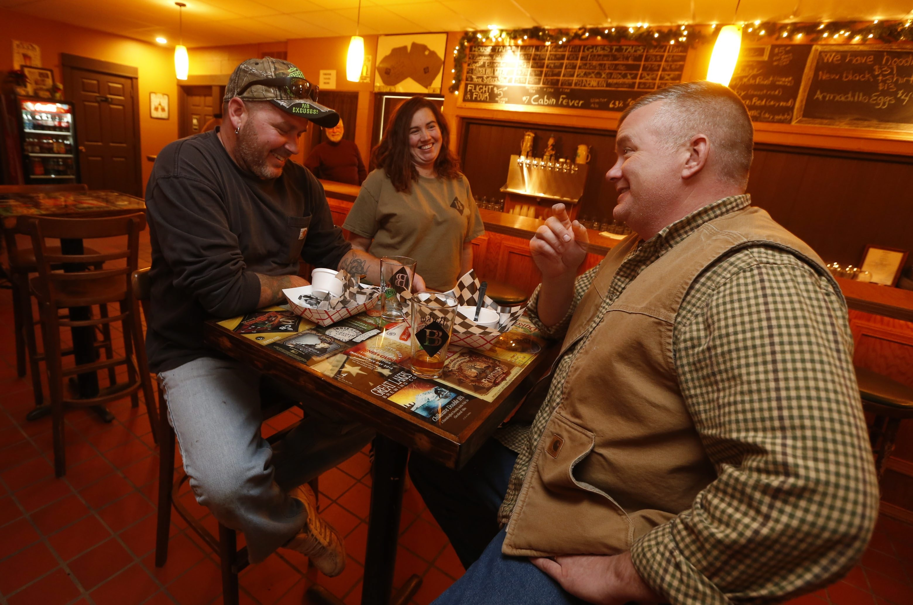 Barker Brewing owner Erin Goodlander checks in with lunch customers Lance Wilson, left, of Newfane, and Bob Fritton of Gasport earlier this month.