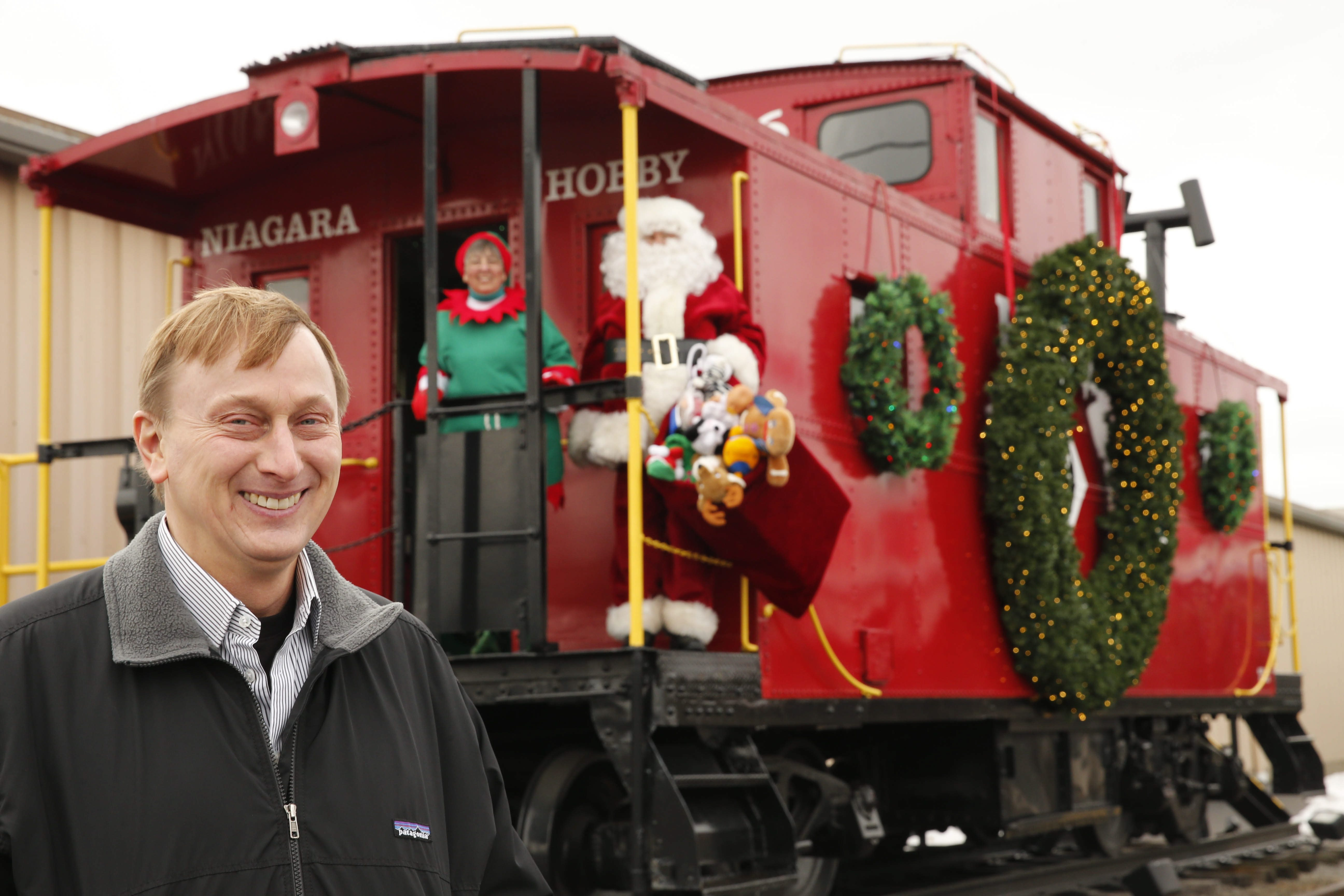 John S. Kavulich II, president of Niagara Hobby & Craft Mart, hosts Santa and an elf at the restored 1949 caboose outside the Cheektowaga store last week. Kavulich, who didn't share his father's interest in hobbies and crafts, is nevertheless preserving his legacy by making the store relevant to new customers.