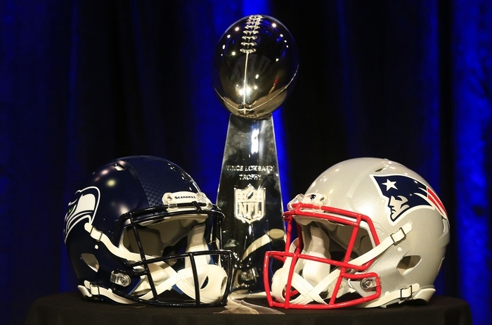 The Vince Lombardi Trophy is displayed between the helmets of  Super Bowl teams Seattle Seahawks and New England Patriots. (Getty Images)