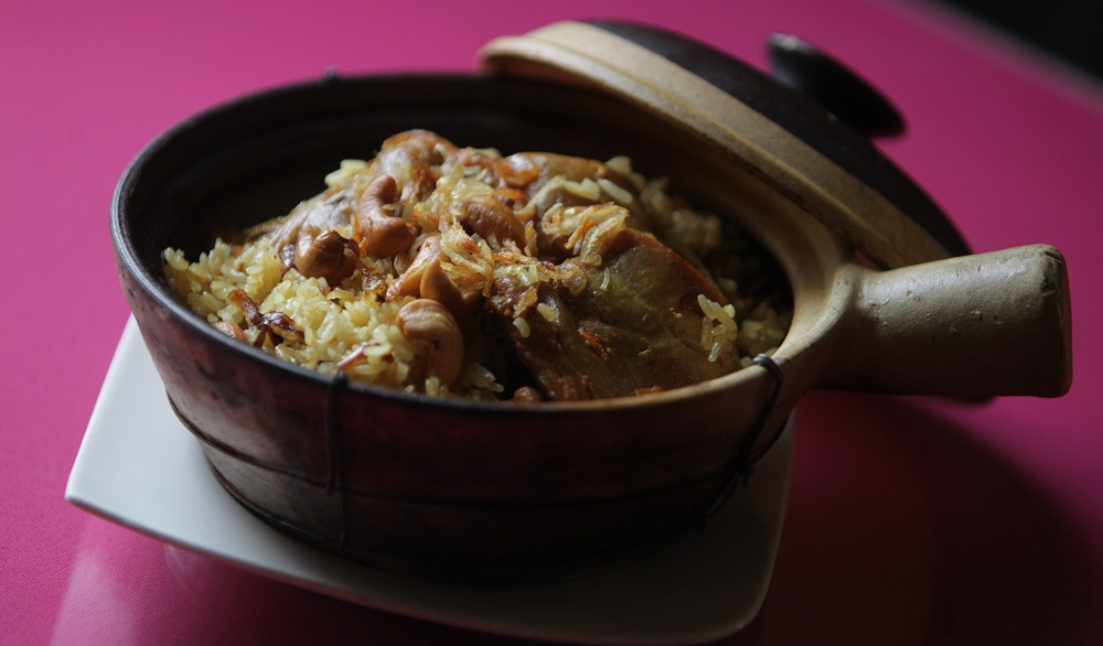 The chicken rice in a clay pot at Thai House is made with chicken and rice marinated with coconut milk, fried onion, cashews and cucumber salad. (Sharon Cantillon/Buffalo News)