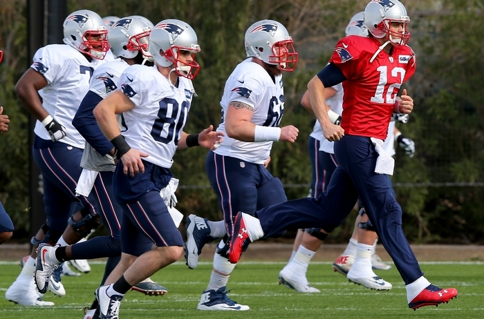 Tom Brady (12) and the rest of his New England Patriots teammates warm up before practice on Thursday at their practice facility in Tempe, Ariz. (Getty Images)