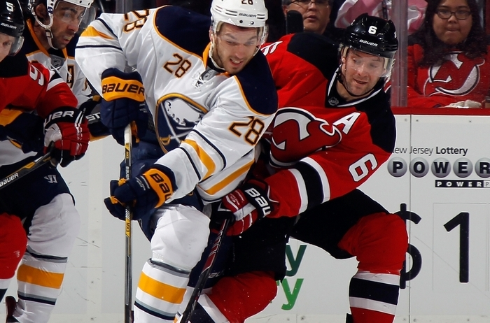 NEWARK, NJ - JANUARY 06: Zemgus Girgensons #28 of the Buffalo Sabres attempts to move the puck around Andy Greene #6 of the New Jersey Devils during the second period at the Prudential Center on January 6, 2015 in Newark, New Jersey.  (Photo by Bruce Bennett/Getty Images)