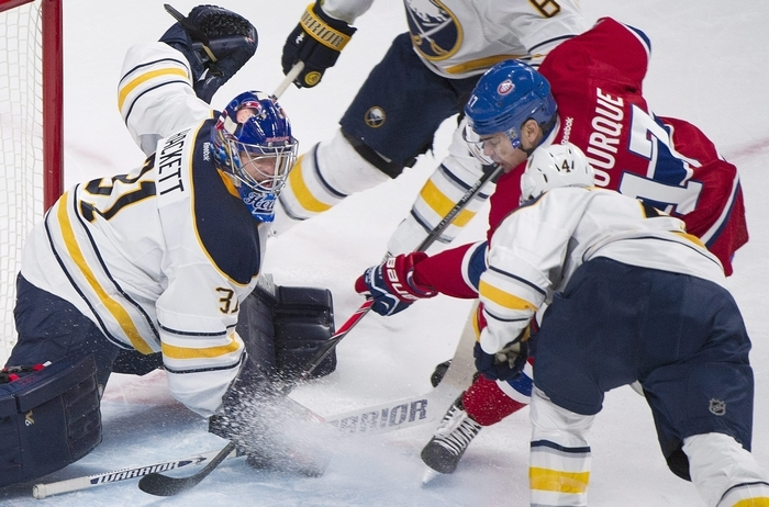 Buffalo Sabres goaltender Matt Hackett, left, makes a save against Montreal Canadiens' Rene Bourque (17) as Sabres' Jamie McBain defends during the first period of an NHL hockey game Tuesday, March 25, 2014, in Montreal. (AP Photo/The Canadian Press, Graham Hughes)