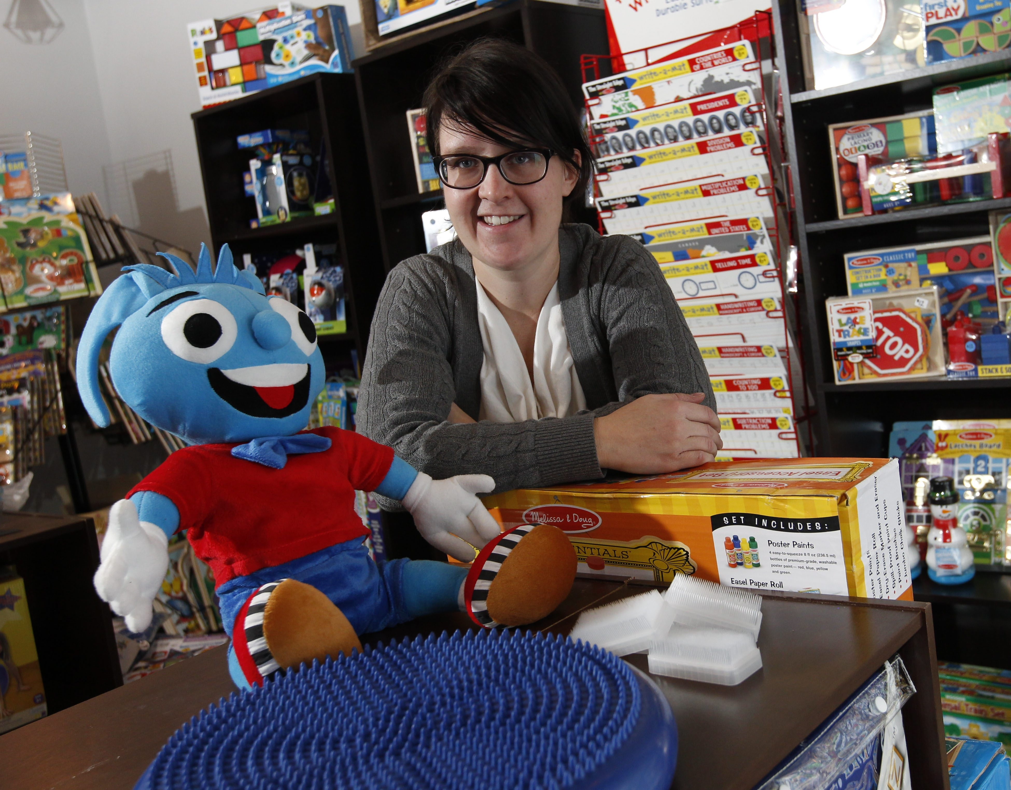 Makes Sense is a relatively new store which specializes in products for children and adults with autism and other special needs.  Owner Stacey Creighton just moved to the store to Main St. in Williamsville.  She's photographed with the doll Heavy Herbert, a dynamic seat cushion and sensory brushes, Wednesday, Jan. 21, 2015.  (Sharon Cantillon/Buffalo News)