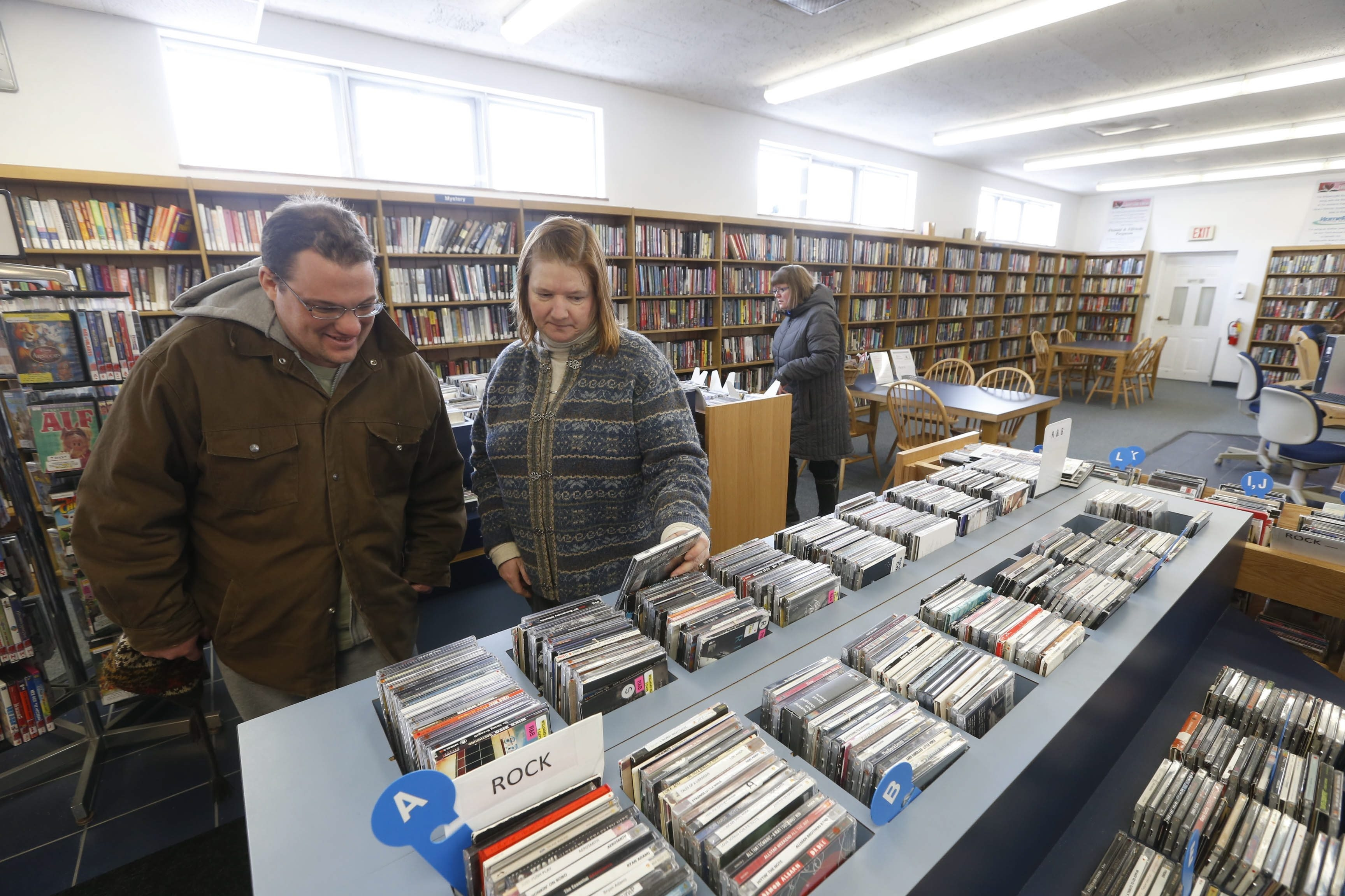 Amherst Library Director Roseanne Butler-Smith helps Williamsville branch visitor and village resident Brian P. Schwab find what he needs. One of the ways the location has survived is through an annual fundraising gala. This year's event is set for Friday.