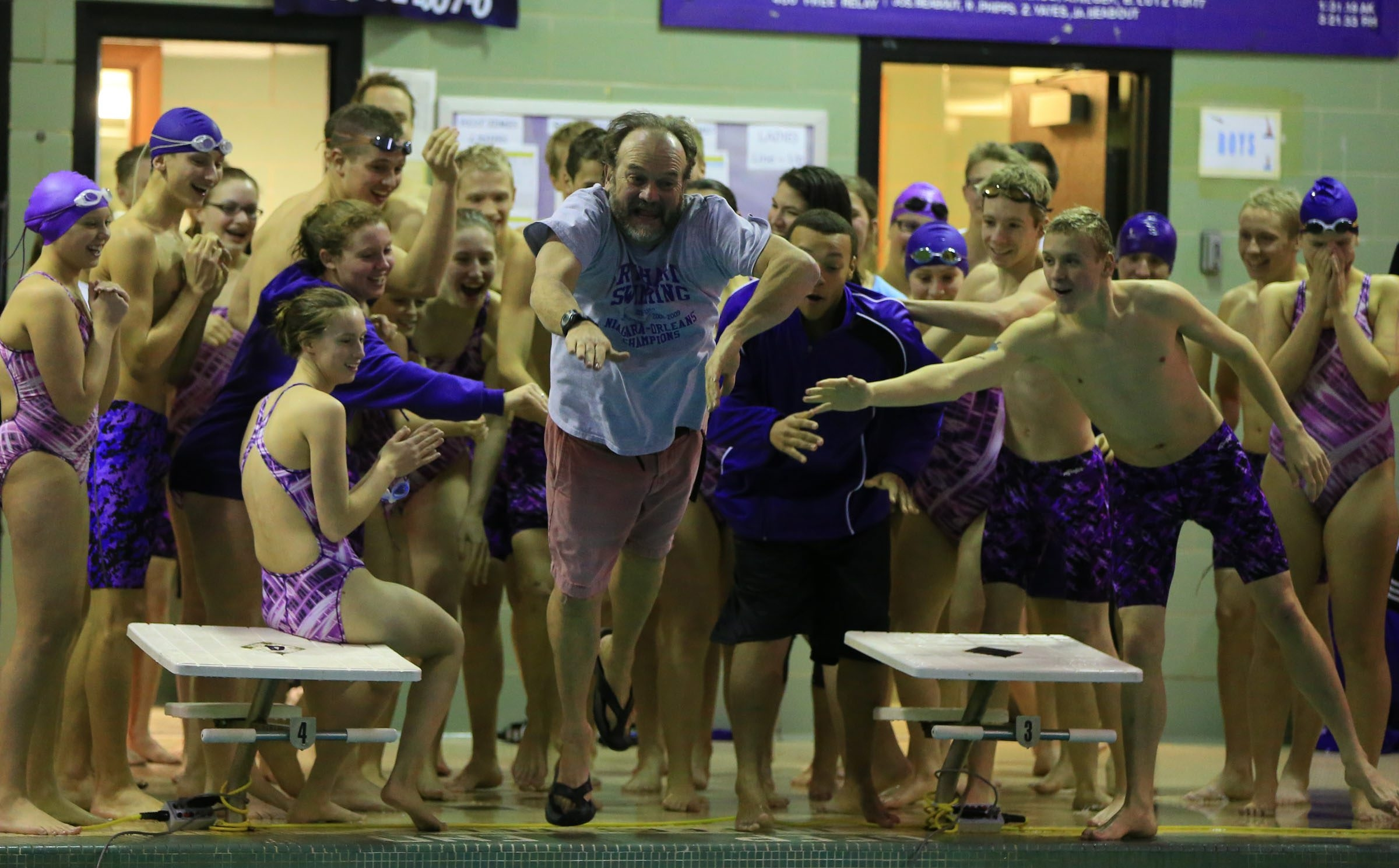 Roy-Hart swimming coach Bruce Matthews heads for the pool after his boys team defeated Akron, 100-51, for its 125th straight dual meet victory and ninth straight Niagara-Orleans League championship.