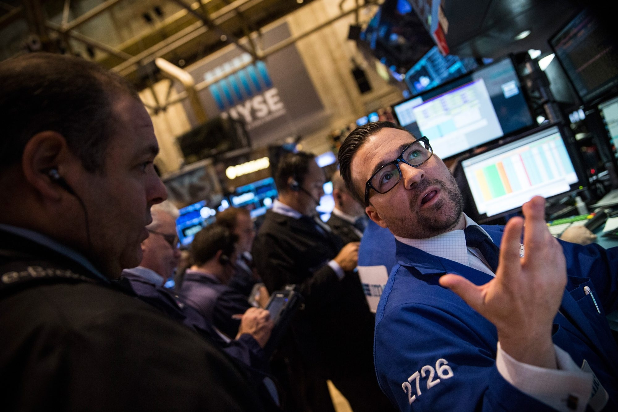 Traders work Monday morning on the floor of the New York Stock Exchange in New York City. The Dow Jones Industrial Average dipped slightly upon opening after Greece held elections over the weekend.