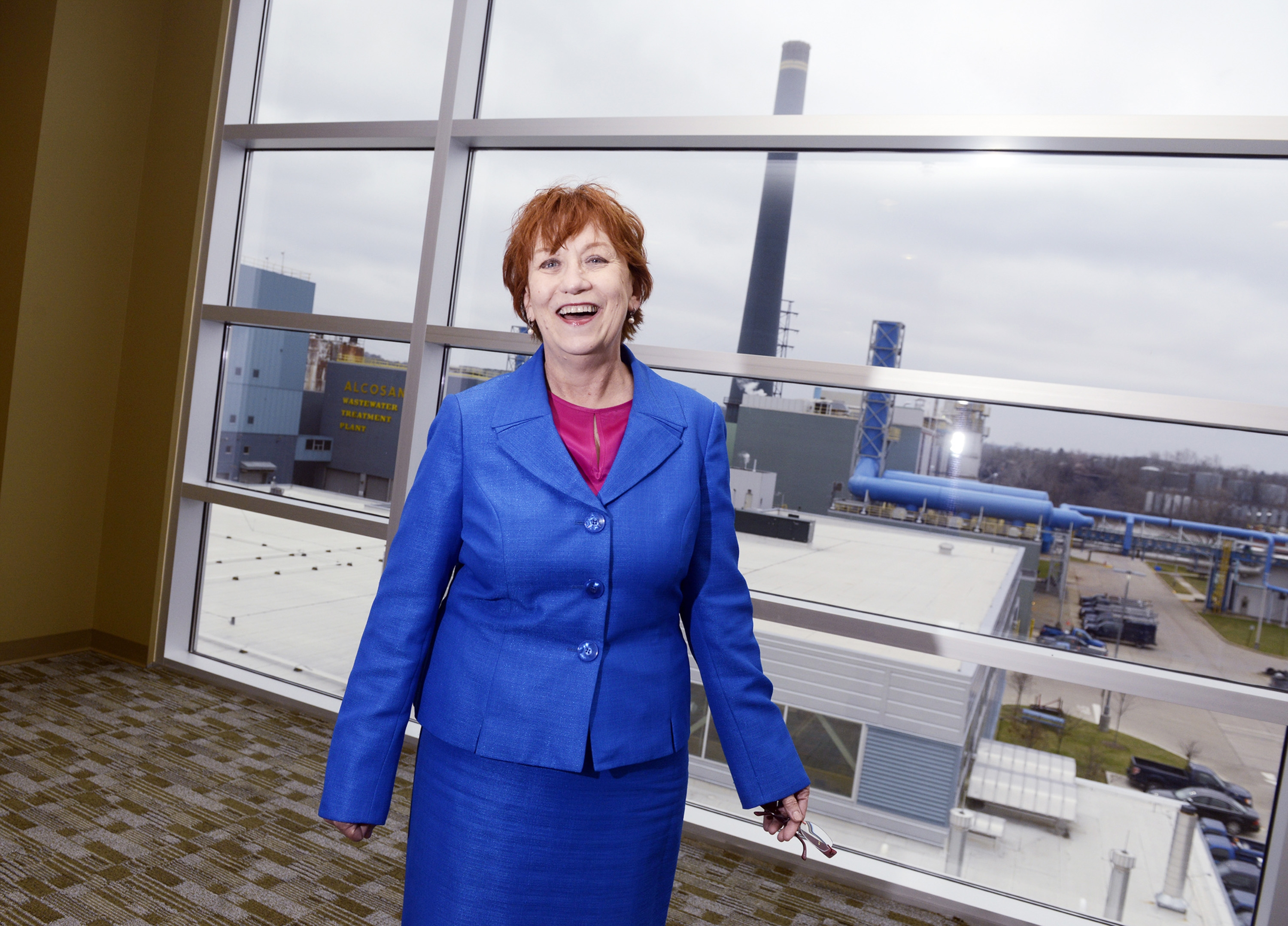 Jeanne Clark, public information officer for Alcosan (Allegheny County Sanitary Authority), takes a break in her office in Pittsburgh. Clark started her job at Alcosan on her 65th birthday, working past normal retirement age. The wastewater treatment plant is in the background.