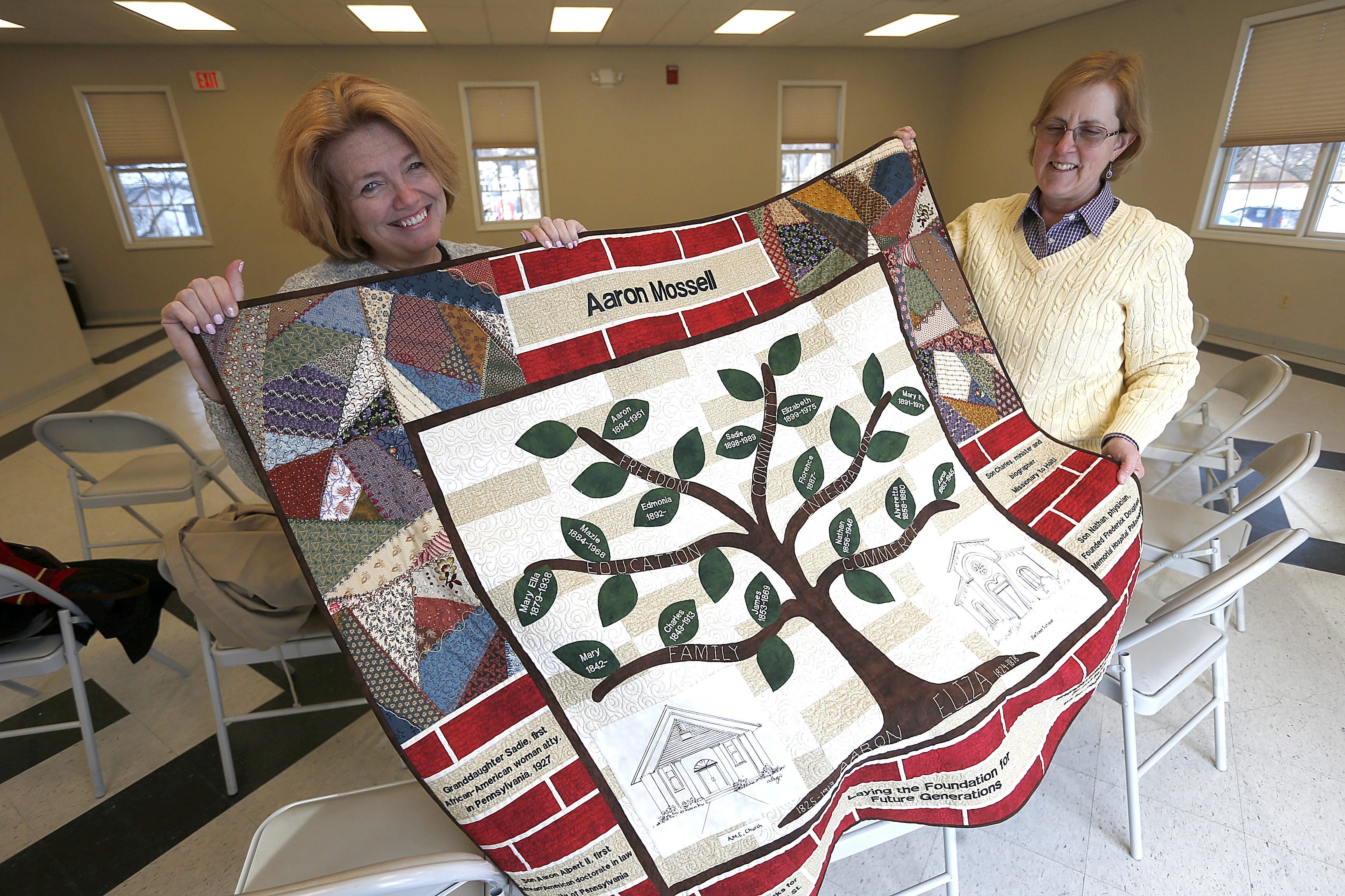 Ellen Martin, left, community coordinator, and Nancy Smith, right, quilt project manager, display a quilt honoring Aaron Mossell, the African-American businessman who forced the desegregation of Lockport public schools in the 1870s.