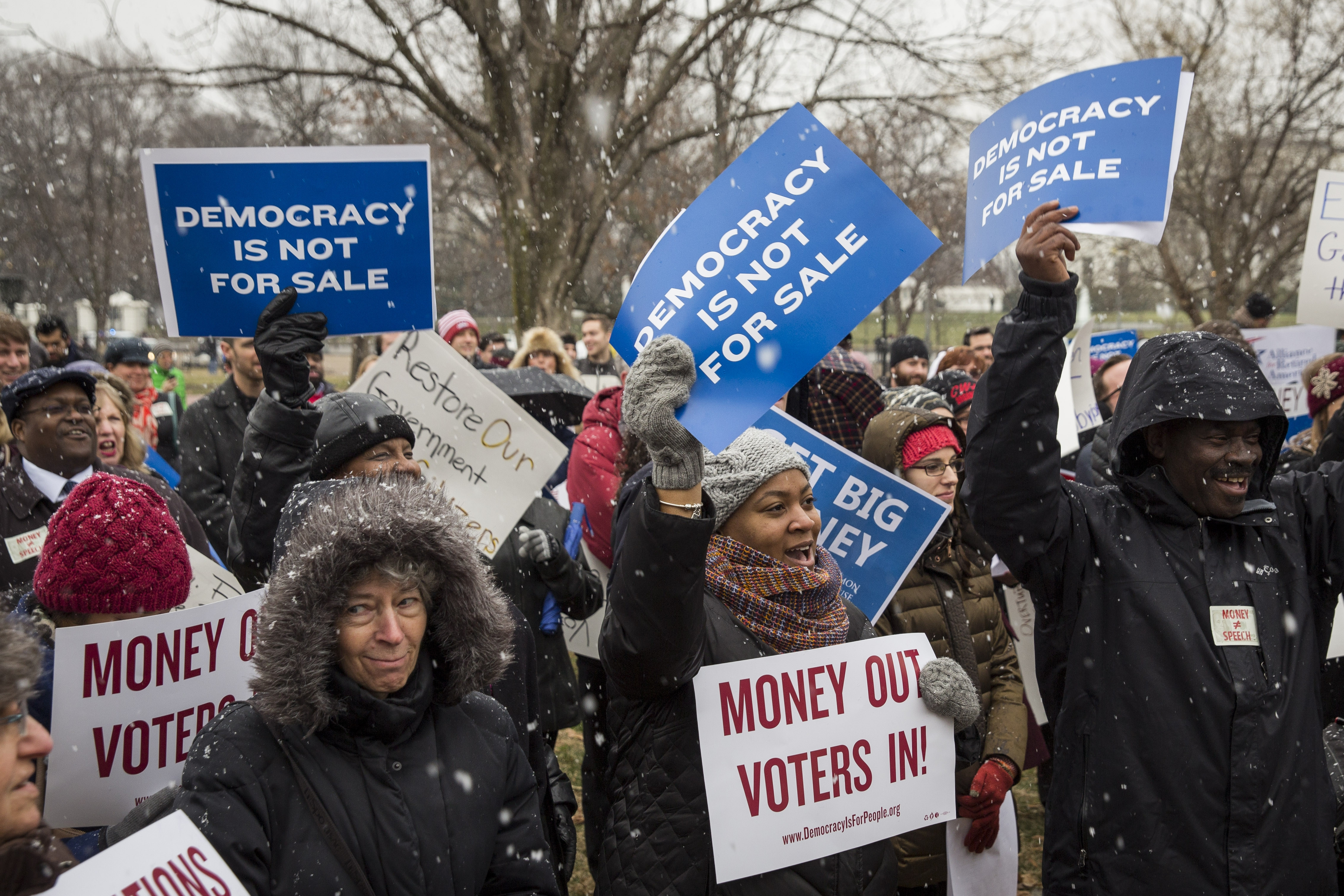Attendees hold signs and cheer during a rally calling for an end to corporate money in politics and to mark the fifth anniversary of the Supreme Court's Citizens United decision, at Lafayette Square near the White House.