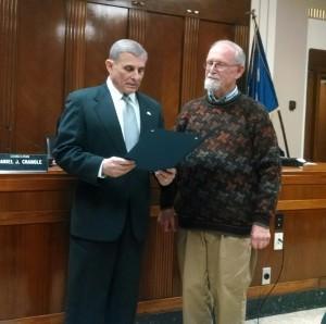 Former Town of Tonawanda historian John Percy, right, receives a proclamation from Town Supervisor Anthony F. Caruana on Monday night.