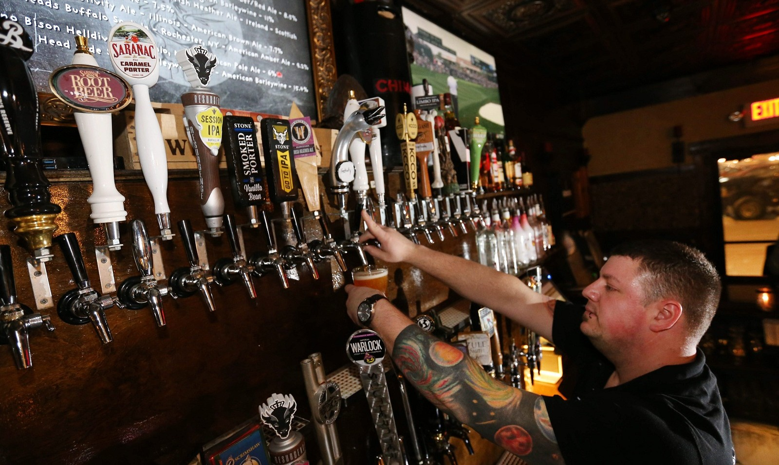 Griffon Pub bartender David Riggs pours a Six Point Bengali Tiger IPA, made in New York City, for a customer. (Sharon Cantillon/Buffalo News)