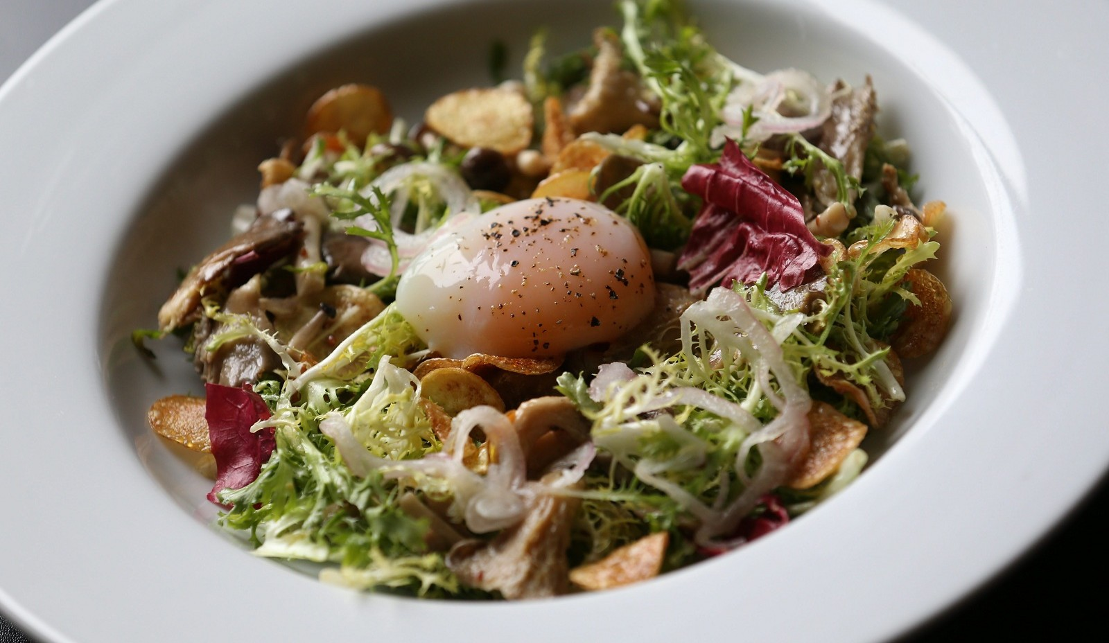The Lyonnaise salad with bitter greens, smoked mushrooms, fingerling chips and a soft egg from Bourbon & Butter. (Sharon Cantillon/Buffalo News file photo)