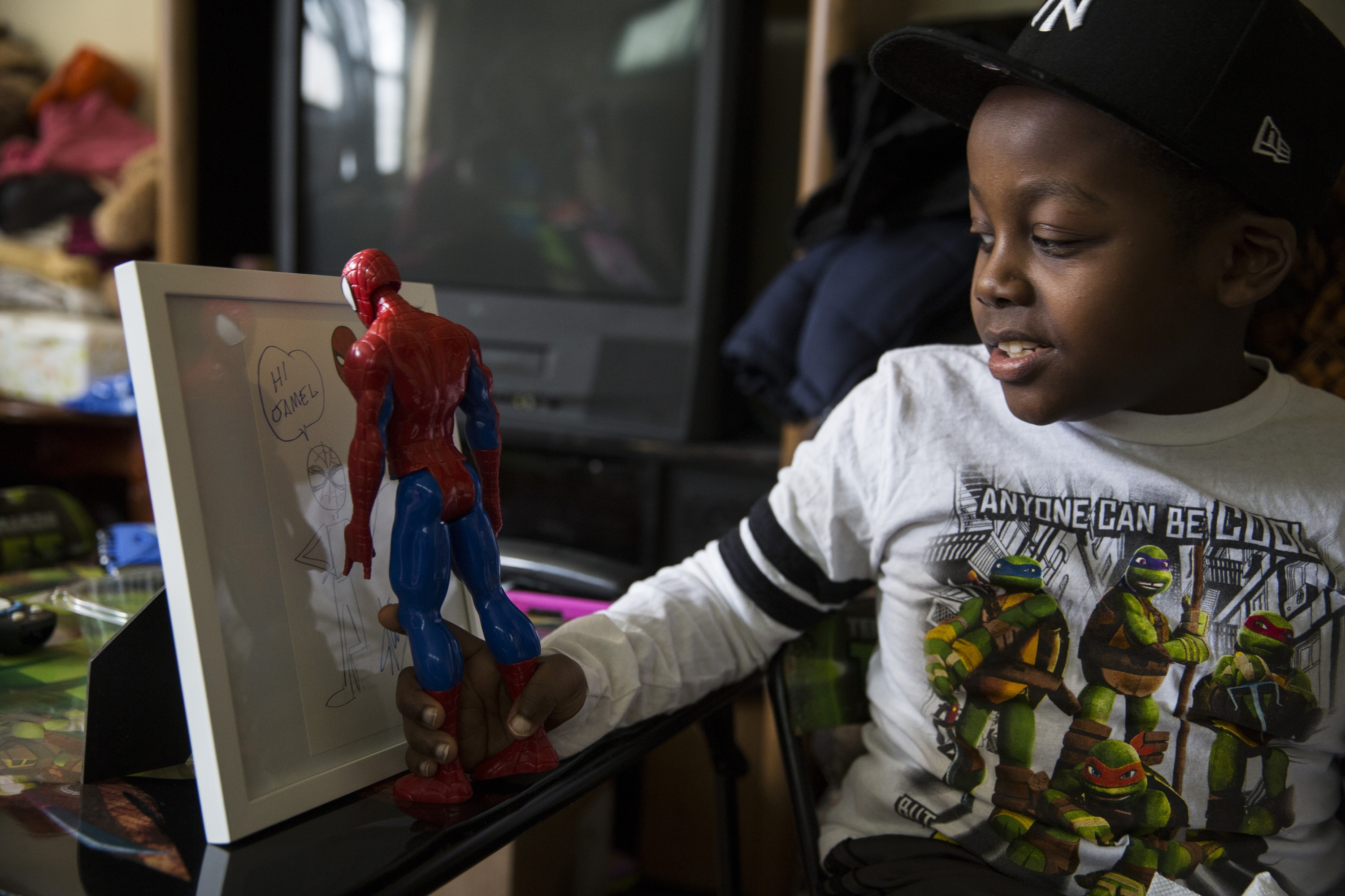 Jamel Hunter and his Spider-Man figure examine a drawing by Stan Lee, the creator of the comic book hero.