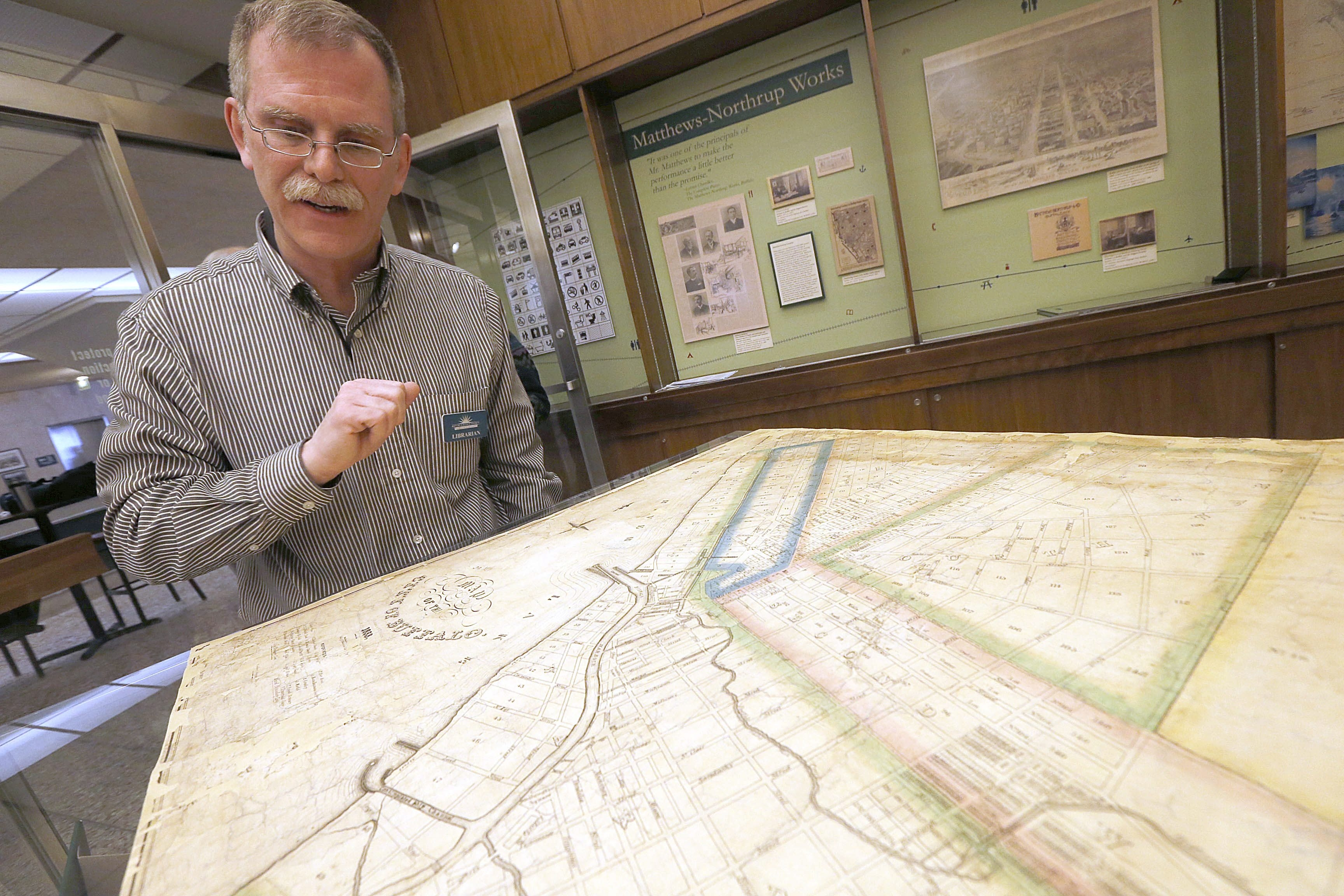 """Charles Alaimo, curator of the """"You Are Here: Buffalo on the Map"""" exhibit at the Central Library, on Monday looks over a restored 1833 map of Buffalo that's on display in the Grosvenor Rare Book Display Room."""