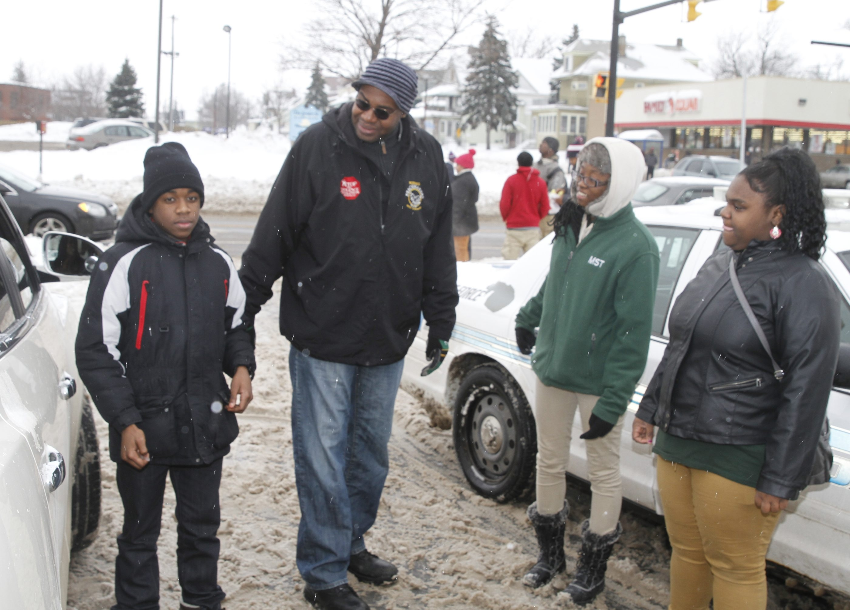 Murray Holman, executive director of Stop the Violence Coalition, talks with students at the corner of East Delavan and Grider.