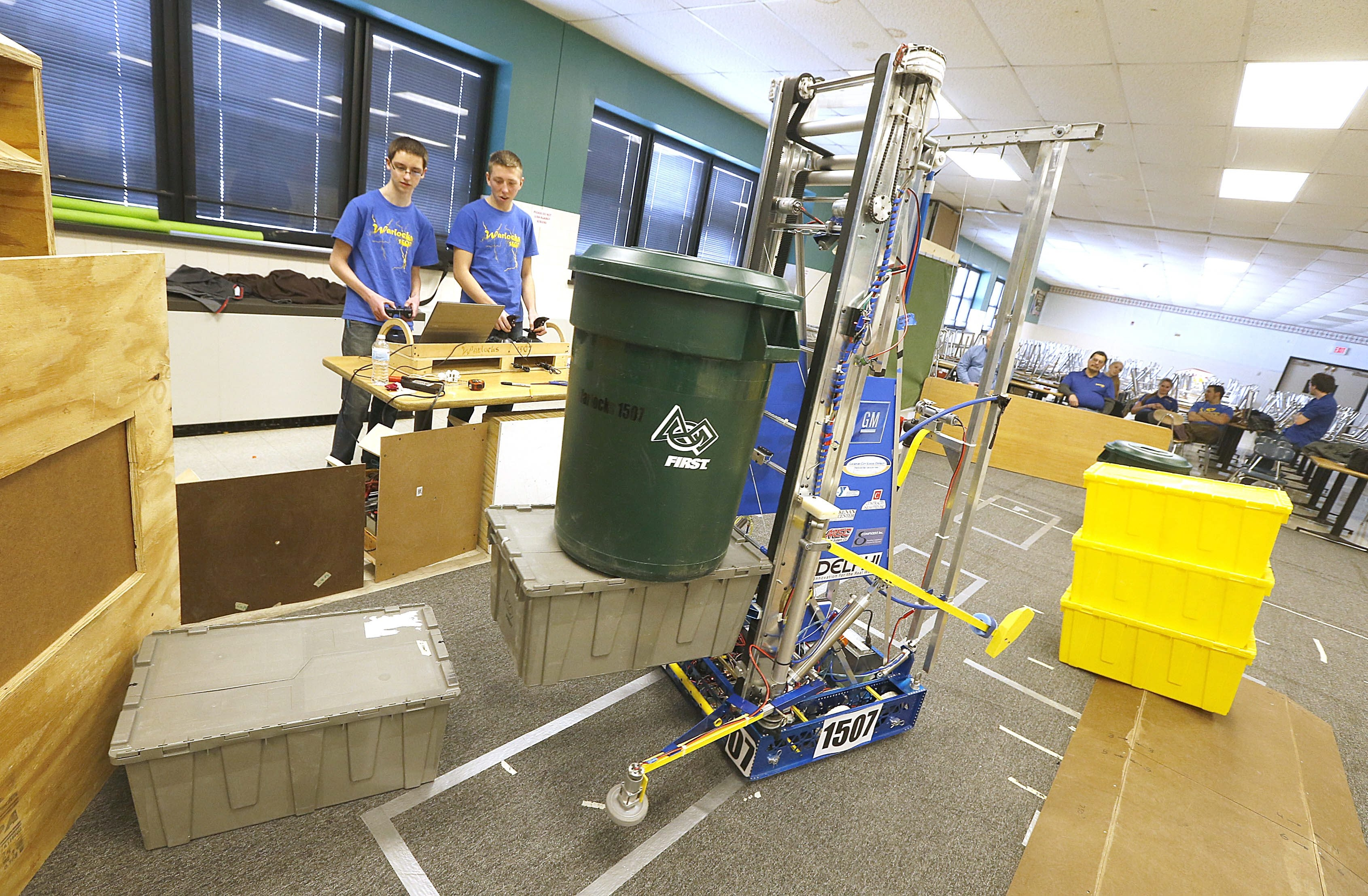 """Students, from left, Nick Brounscheidel and Ken Handley,  with the """"Totezilla"""" robot.  They are members of the Warlocks 1507 drive team in the Lockport High School cafeteria on Monday, Feb. 16, 2015."""