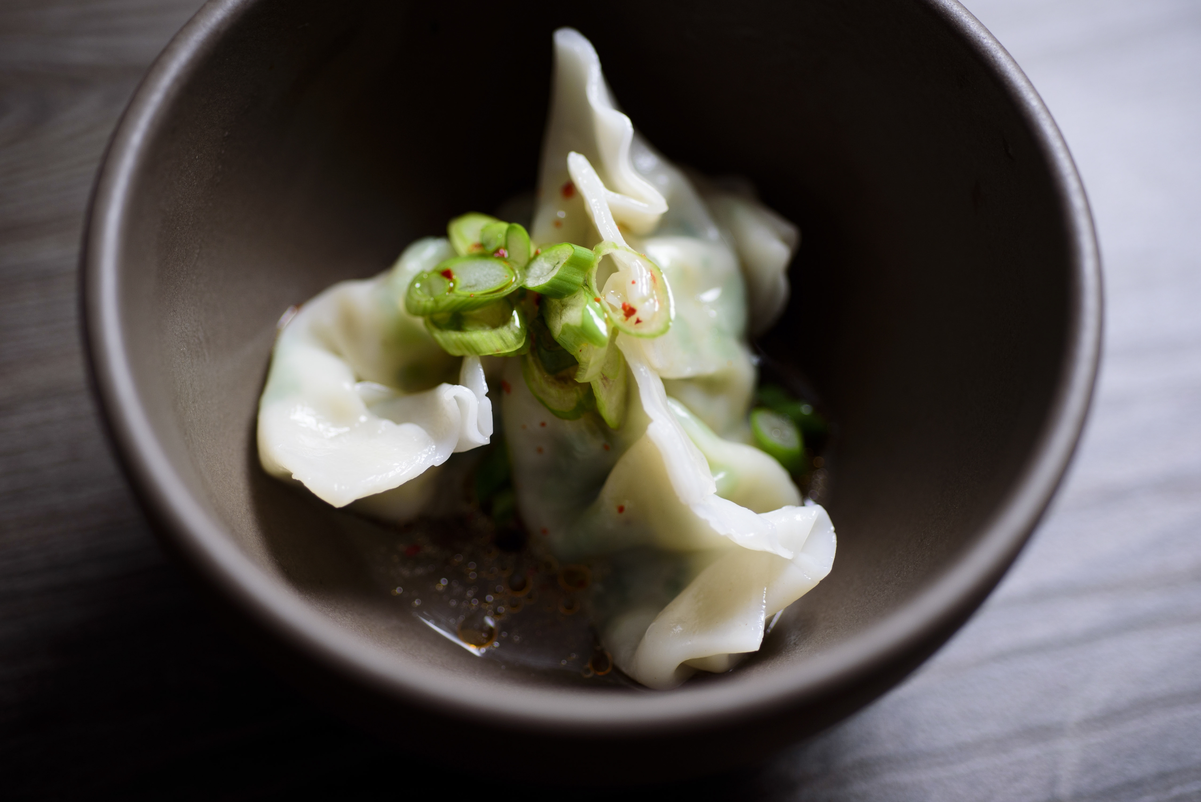 Shrimp and scallop dumplings are dressed with a sauce of spicy sesame oil, rice wine vinegar and slivered scallions.
