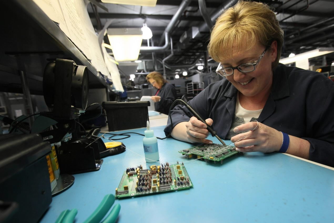 Astronics assembler Edyta Sokolowski puts together a circuit board that will go into an airplane lighting system.