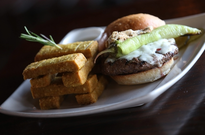 This is the hot mama burger, right, with stuffed banana peppers and aged provolone. On the left are garbanzo bean fries with hempseed ranch dip. (Sharon Cantillon/Buffalo News)