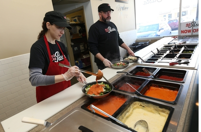 Prep cook Lynn Lombardo, left, and chef Mike McGee help customers build their own pasta dishes at In & Out Pasta in Amherst . (Sharon Cantillon/Buffalo News)