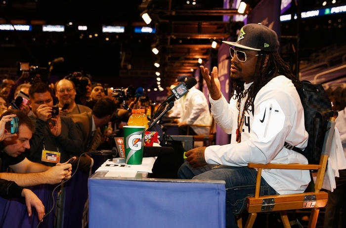 "Seattle's Marshawn Lynch ""addresses"" reporters during Super Bowl Media Day in Phoenix Tuesday. Lynch bolted after five minutes. (Getty Images)"