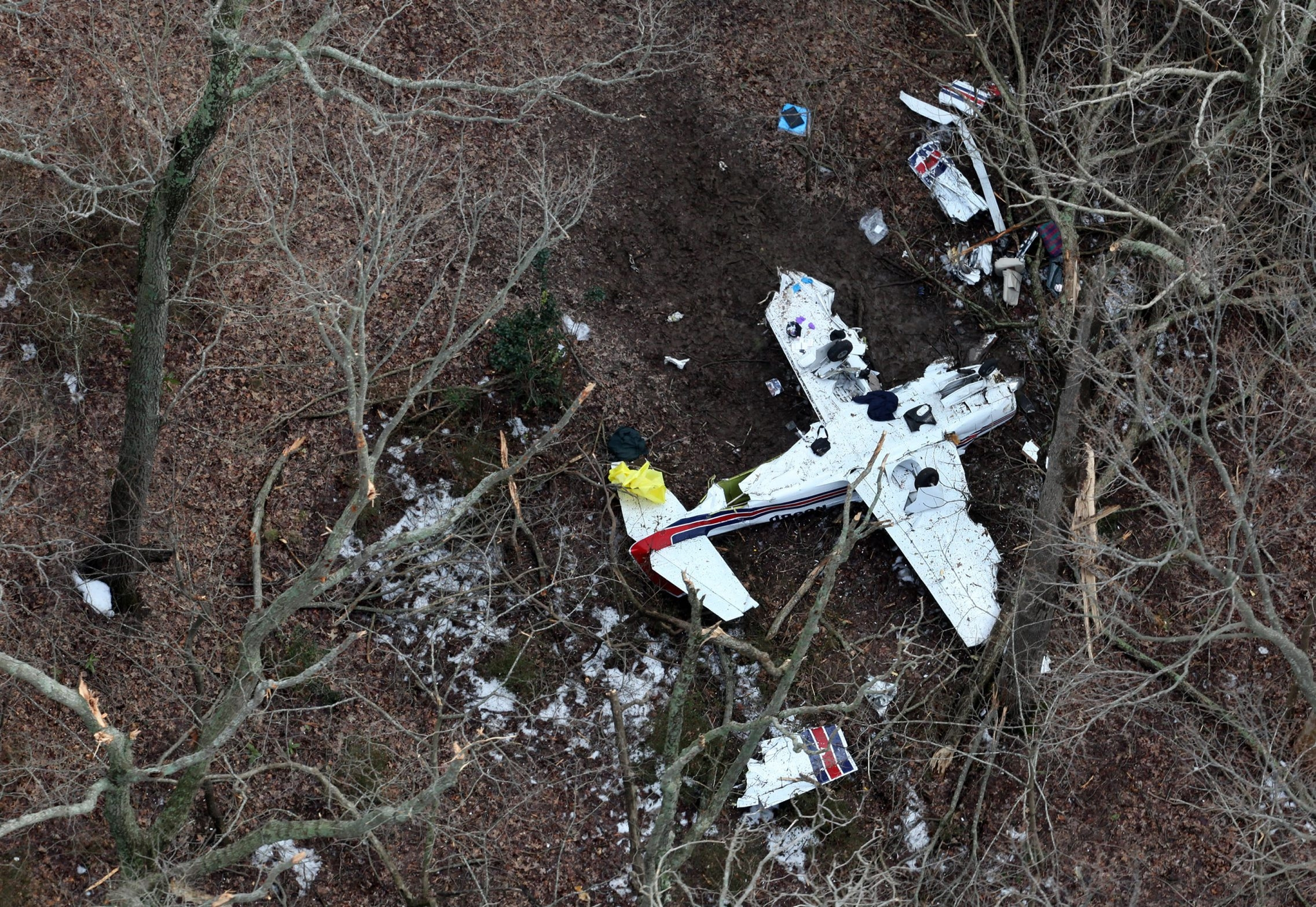 The upside-down wreckage of a four-seat Mooney M20F aircraft is seen on the grounds of the Norfolk Botanical Garden, just outside of Norfolk International Airport on Wednesday, March 4, 2015.  Three people were confirmed dead after the plane crashed while on approach to the airport. (Martin Smith-Rodden | The Virginian-Pilot)