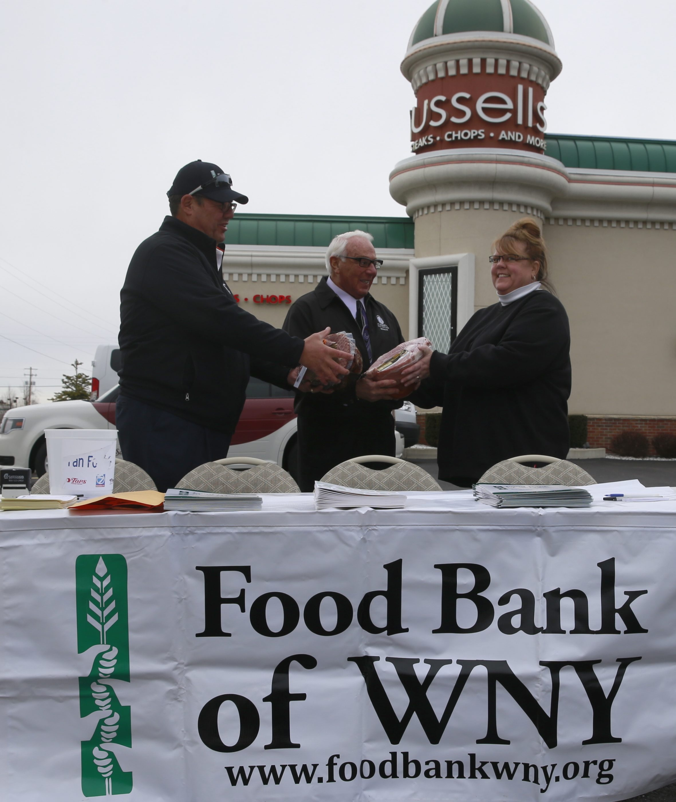 Mike Billoni, marketing and public relations director of the Food Bank of WNY, left, and Russell Salvatore accept hams from Kristen Forster of North Tonawanda at Tuesday's Ham-a-Lot.