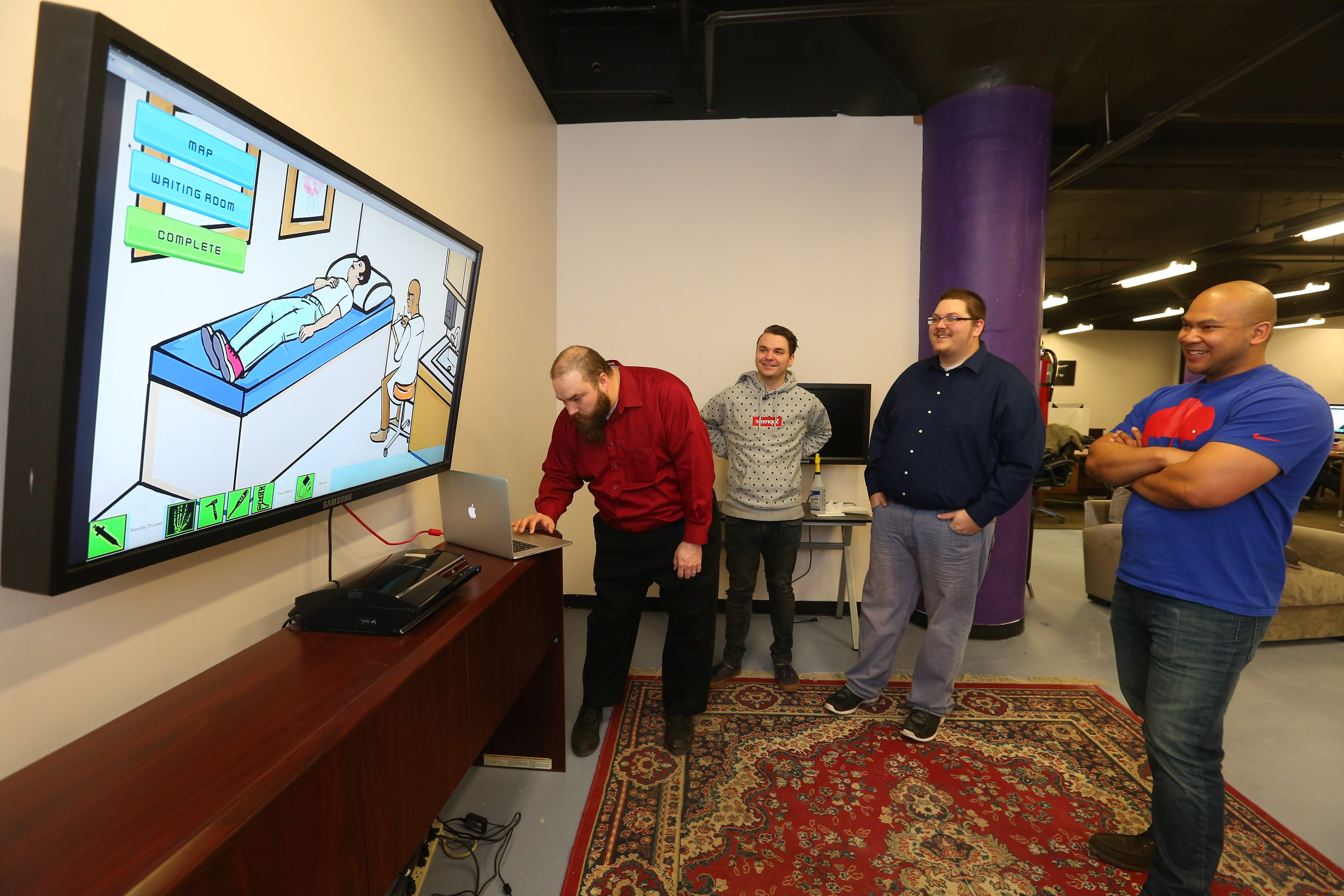 """Bill Stewart, left, types into his laptop as Eric Keller, center, and Dan Griggs  watches. Stewart and Griggs """"Queen City Careers"""" is the front-runner in Buffalo's computer game competition."""