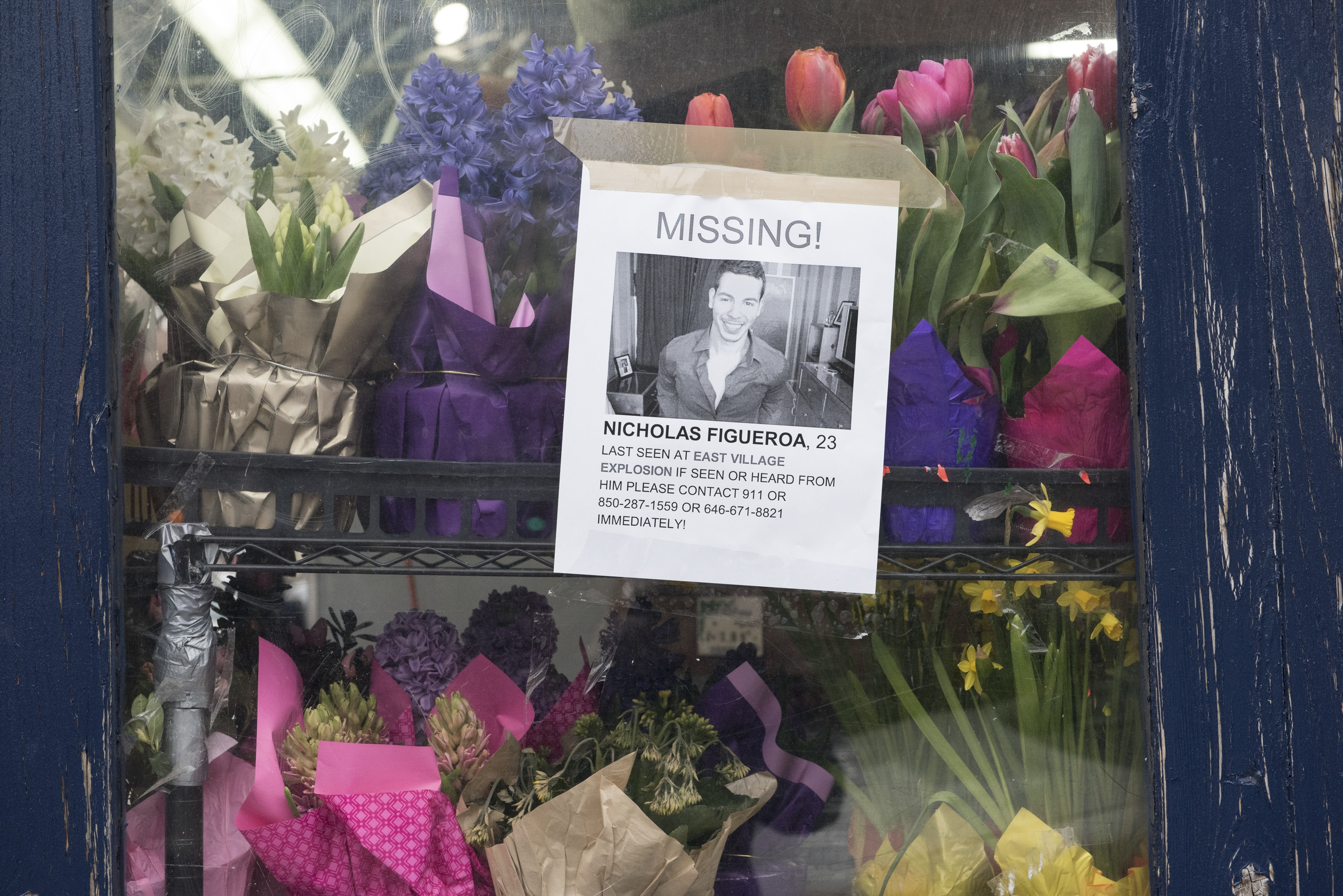 A poster seeks information on Nicholas Figueroa, missing in Thursday's explosion.