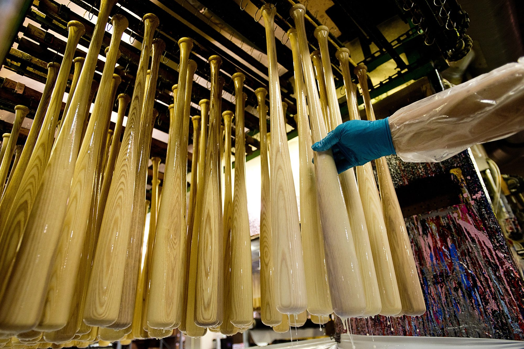 Varnished baseball bats are hung on racks to dry before shipment at the Louisville Slugger Museum & Factory. Parent company Hillerich & Bradsby is selling the bat manufacturer to Wilson Sporting Goods, a brand of Helsinki-based Amer Sports.