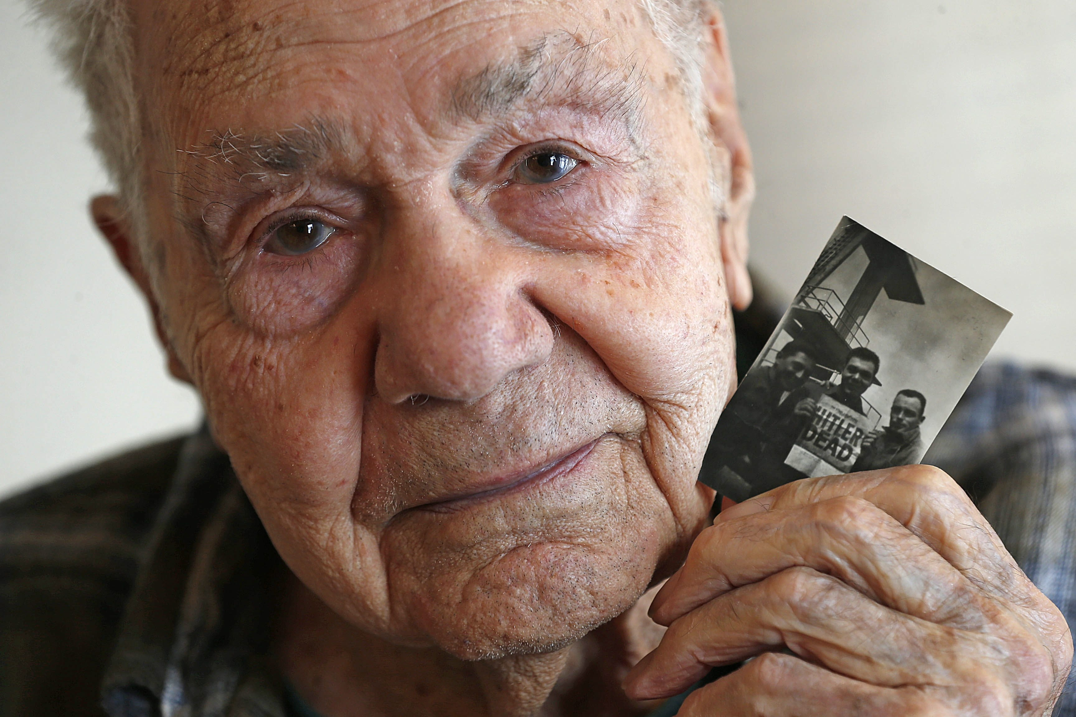 "Phillip T. Paonessa Sr. holds a WWII photo of him in Germany, with two buddies, holding a newspaper headlined ""HITLER DEAD."""