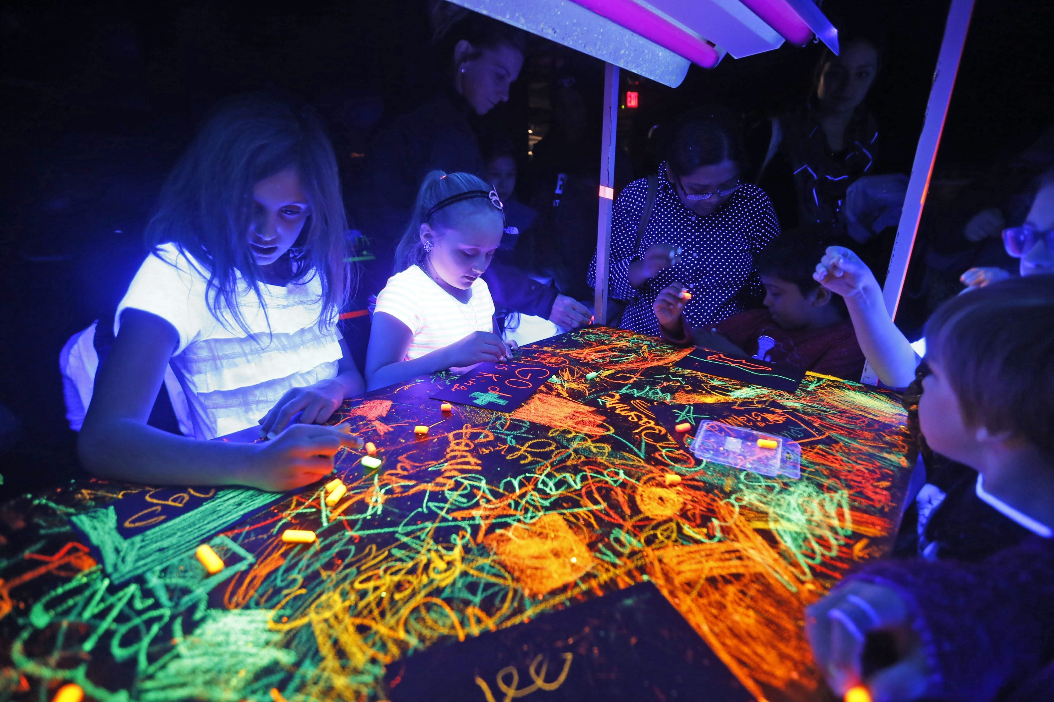 "Children draw on a surface illuminated with black lights during the Buffalo Museum of Science's first MessFest on Sunday. ""Making a mess is a great way to the hook, to get kids interested in science,"" said the museum's Karen Wallace."