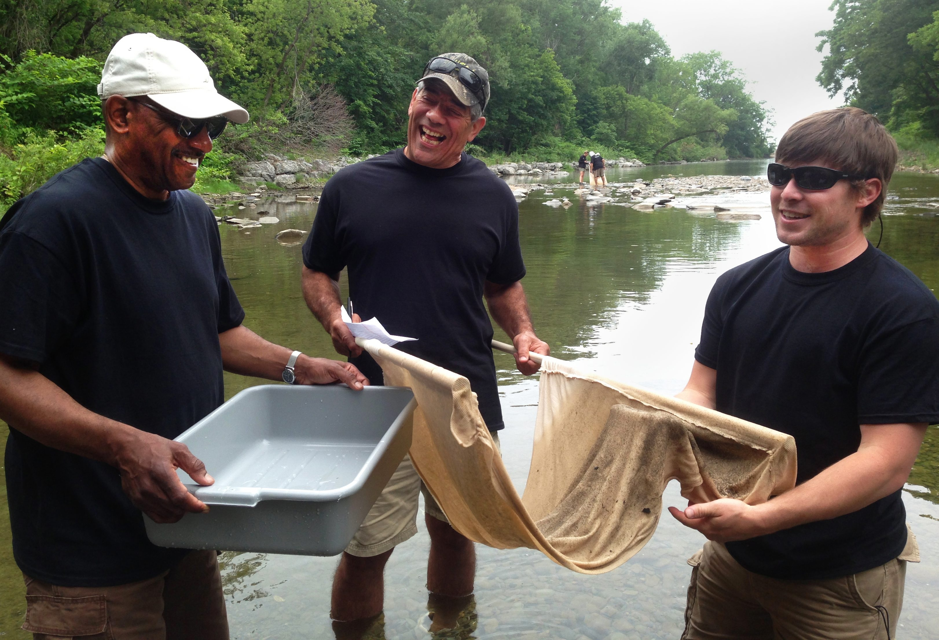 Dr. Carl Williams, Willie Morales and Derek Jon Conant seine a stream to check for insect life and water quality. Conservation projects are undertaken by a variety of area organizations.
