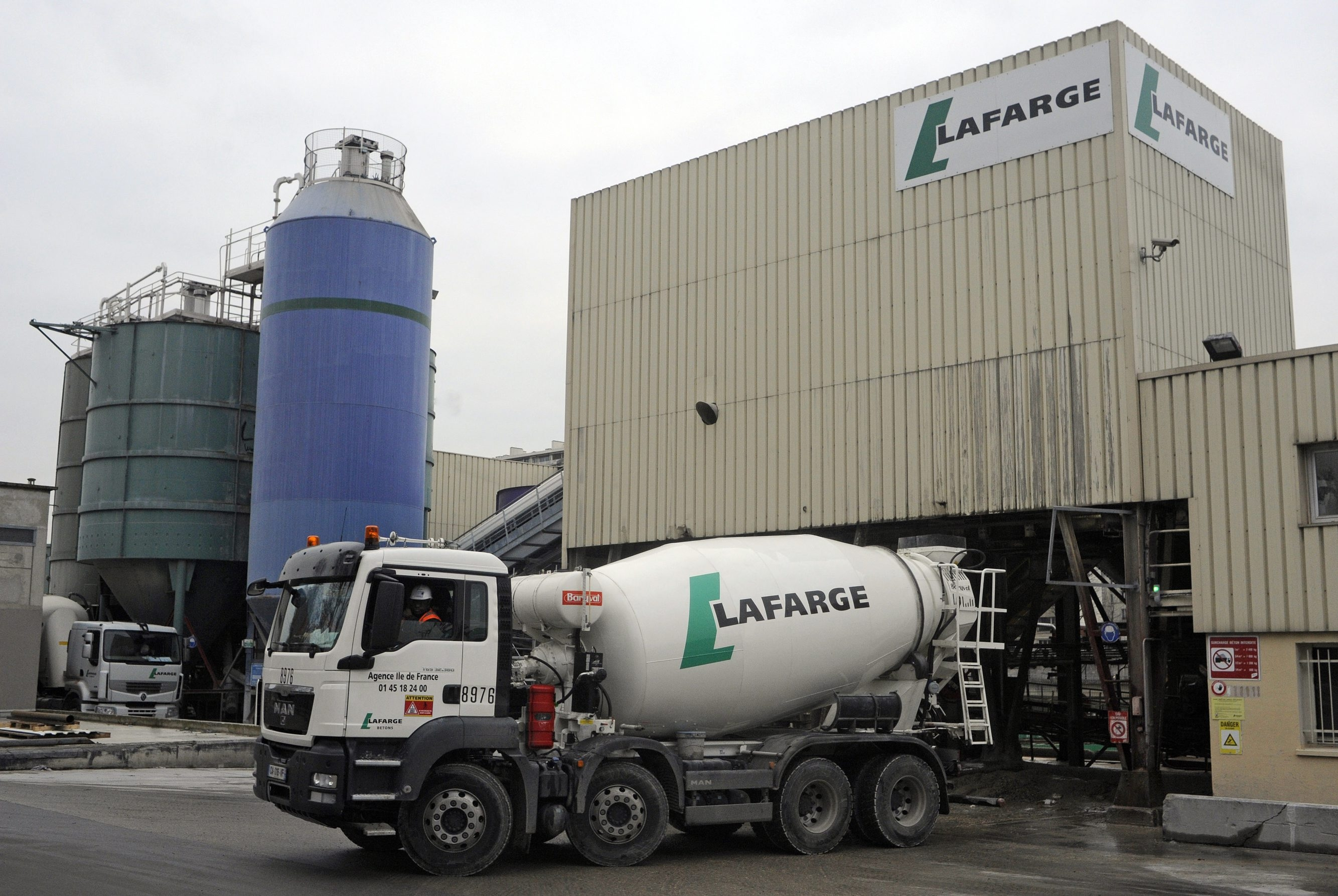 A Lafarge cement mixer truck is driven from the refilling station at Lafarge SA's depot in Paris. Holcim Ltd. and Lafarge SA agreed to a merger to create the world's biggest cement maker with more than $40 billion in sales.